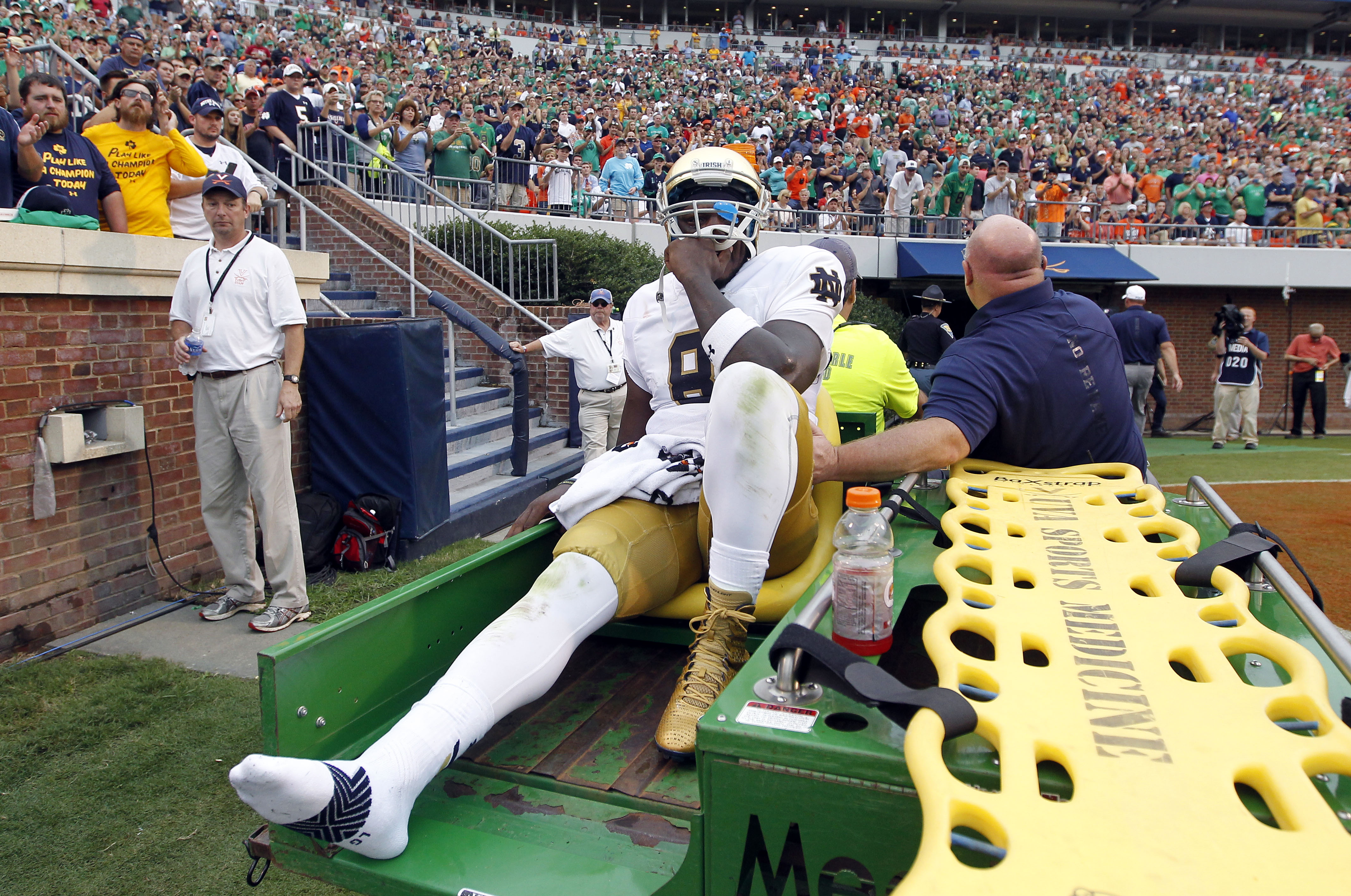 Notre Dame quarterback Malik Zaire (8) is driven off the field after injuring his right ankle during an NCAA college football game against Virginia, Saturday, Sept. 12, 2015, in Charlottesville, Va.  Notre Dame defeated Virginia 34-27. (AP Photo/Andrew Sh