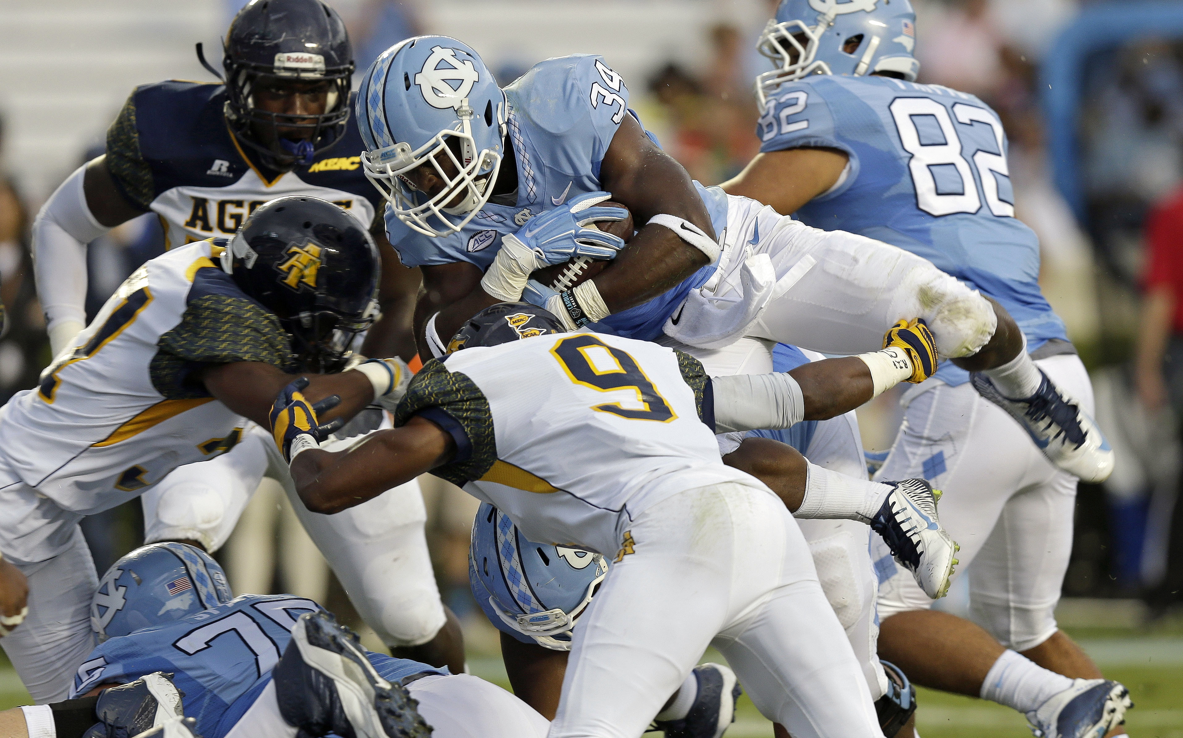 North Carolina's Elijah Hood (34) dives over North Carolina A&T's Zerius Lockhart (9) during the first half of an NCAA college football game in Chapel Hill, N.C., Saturday, Sept. 12, 2015. Hood scored a touchdown on the play. (AP Photo/Gerry Broome)