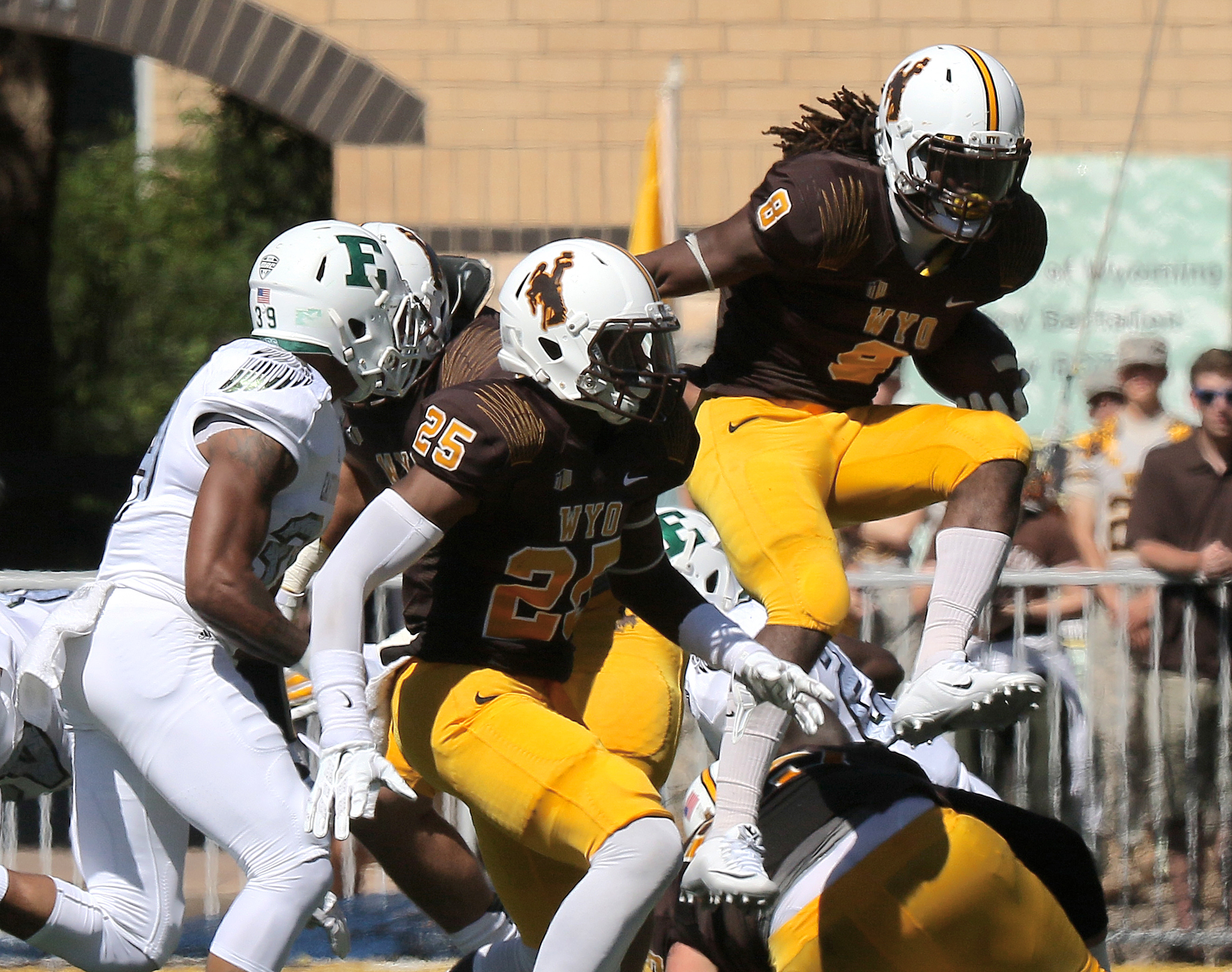 University of Wyoming running back Brian Hill hurdles a pile of players in the first half of an NCAA college football game against Eastern Michigan University on Saturday, Sept. 12, 2015, in Laramie, Wyo. (AP Photo/Blaine McCartney)