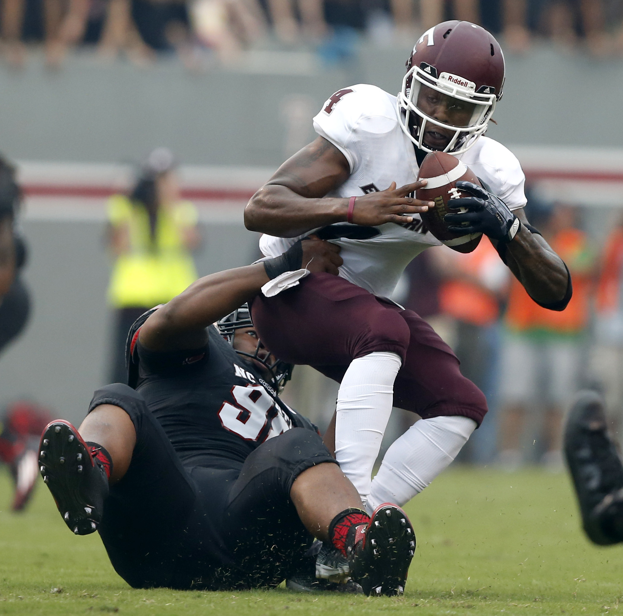 North Carolina State defensive tackle B.J. Hill (98) grabs Eastern Kentucky quarterback Bennie Coney (4) during the first half of an NCAA college football game Saturday, Sept. 12, 2015, in Raleigh, N.C. (Ethan Hyman/The News & Observer via AP) MANDATORY C