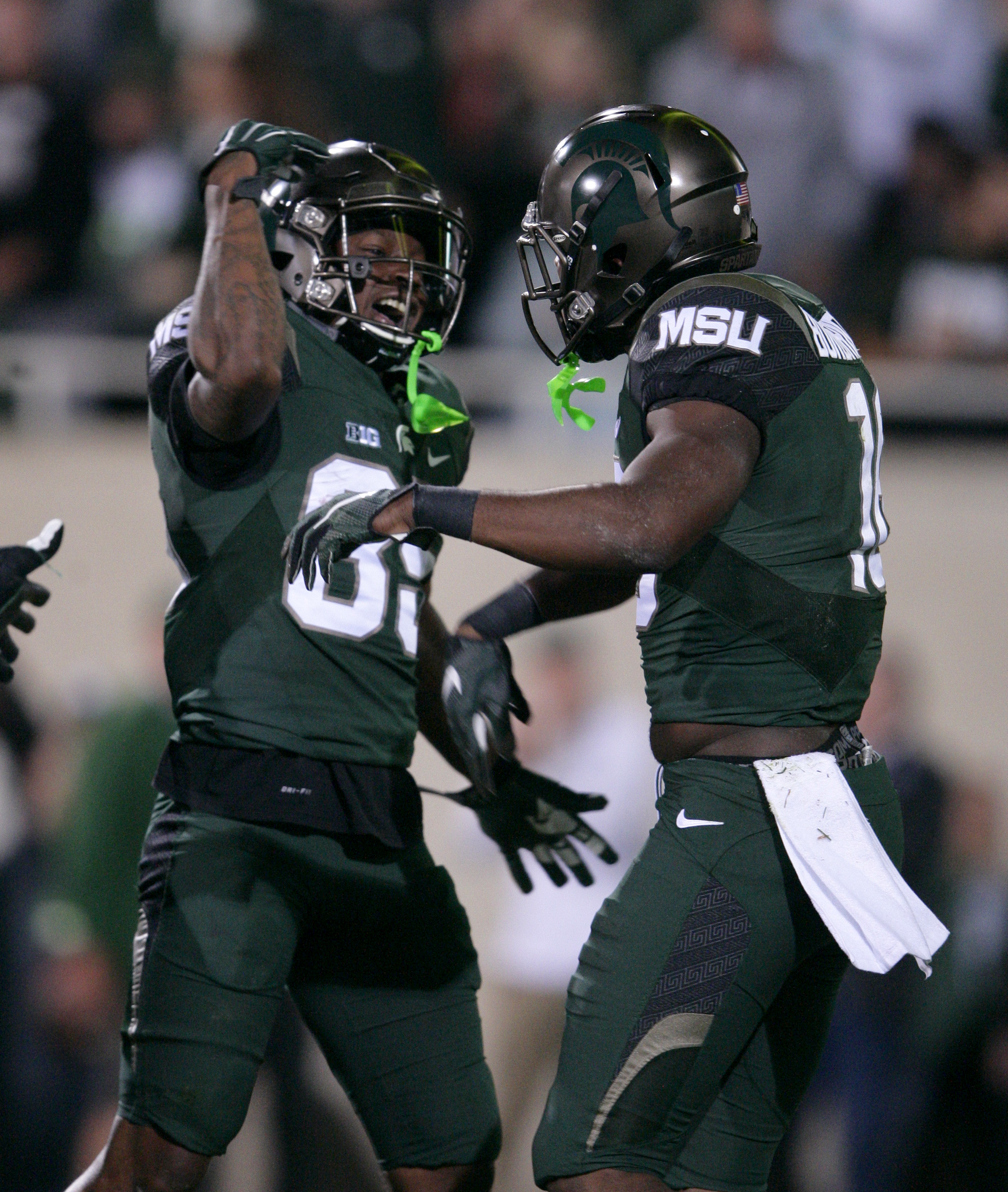 Michigan State's Aaron Burbridge, right, and Macgarrett Kings Jr. celebrate Burbridge's touchdown against Oregon during the second quarter of an NCAA college football game, Saturday, Sept. 12, 2015, in East Lansing, Mich. (AP Photo/Al Goldis)