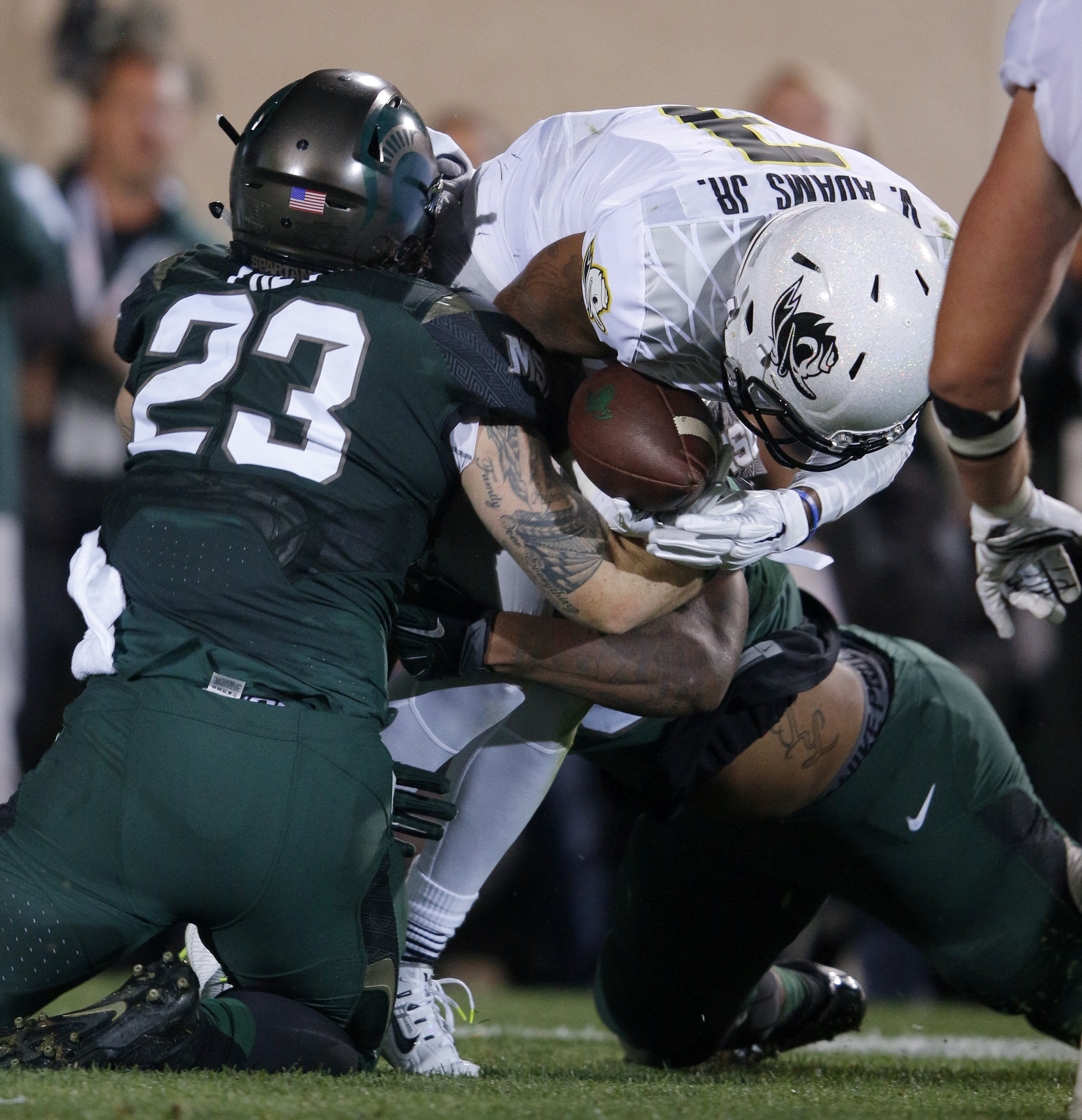 Oregon quarterback Vernon Adams Jr., center, is sacked by Michigan State's Chris Frey (23) and Demetrius Cooper, rear, during the first quarter of an NCAA college football game, Saturday, Sept. 12, 2015, in East Lansing, Mich. (AP Photo/Al Goldis)