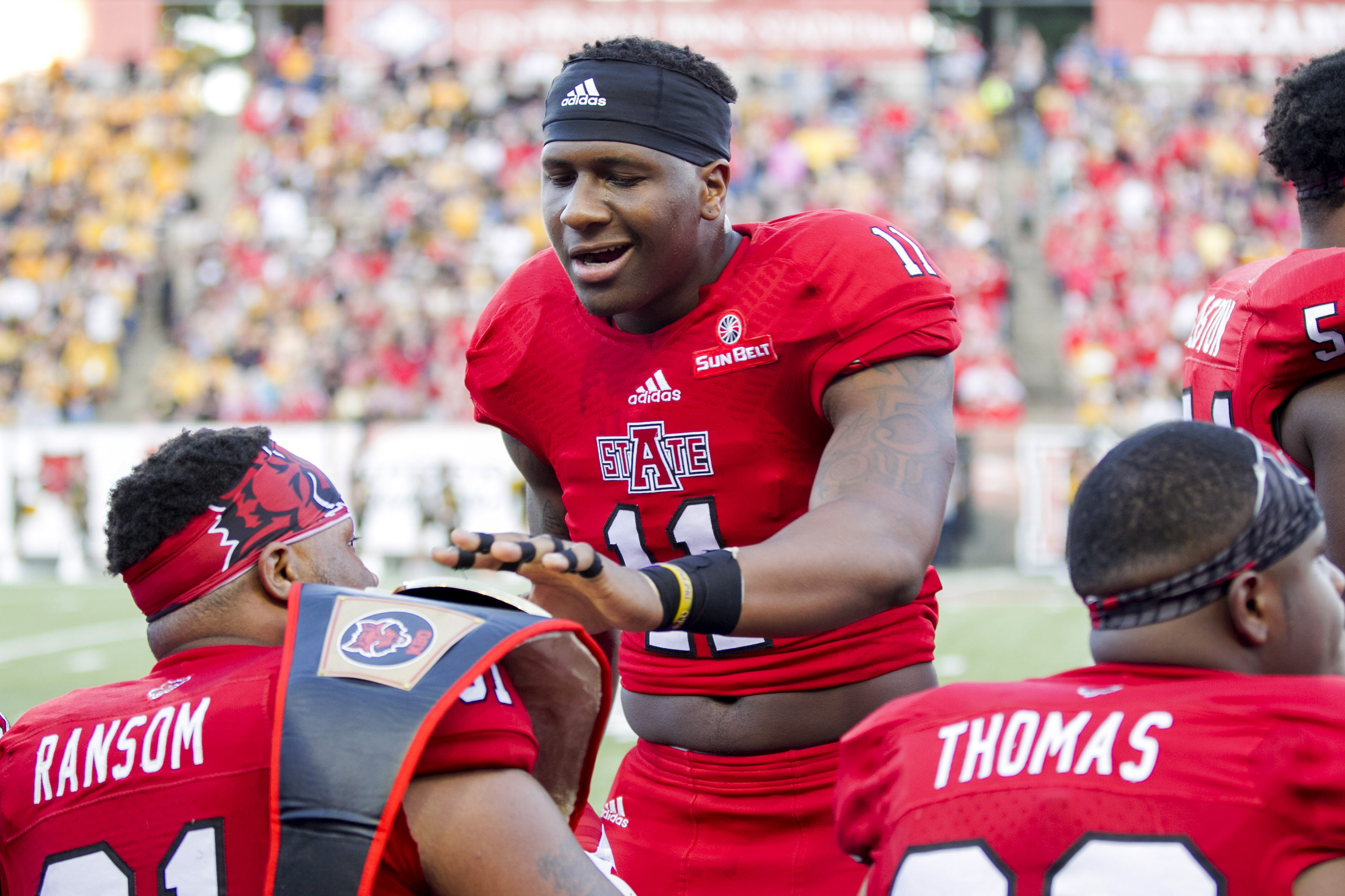 Arkansas State defensive end Ja'Von Rolland-Jones (11) hands off a wresting belt to defensive lineman Donovan Ransom (91) after an interception during an NCAA college football game Saturday, Sept. 12, 2015, in Jonesboro, Ark. (AP Photo/Gareth Patterson)