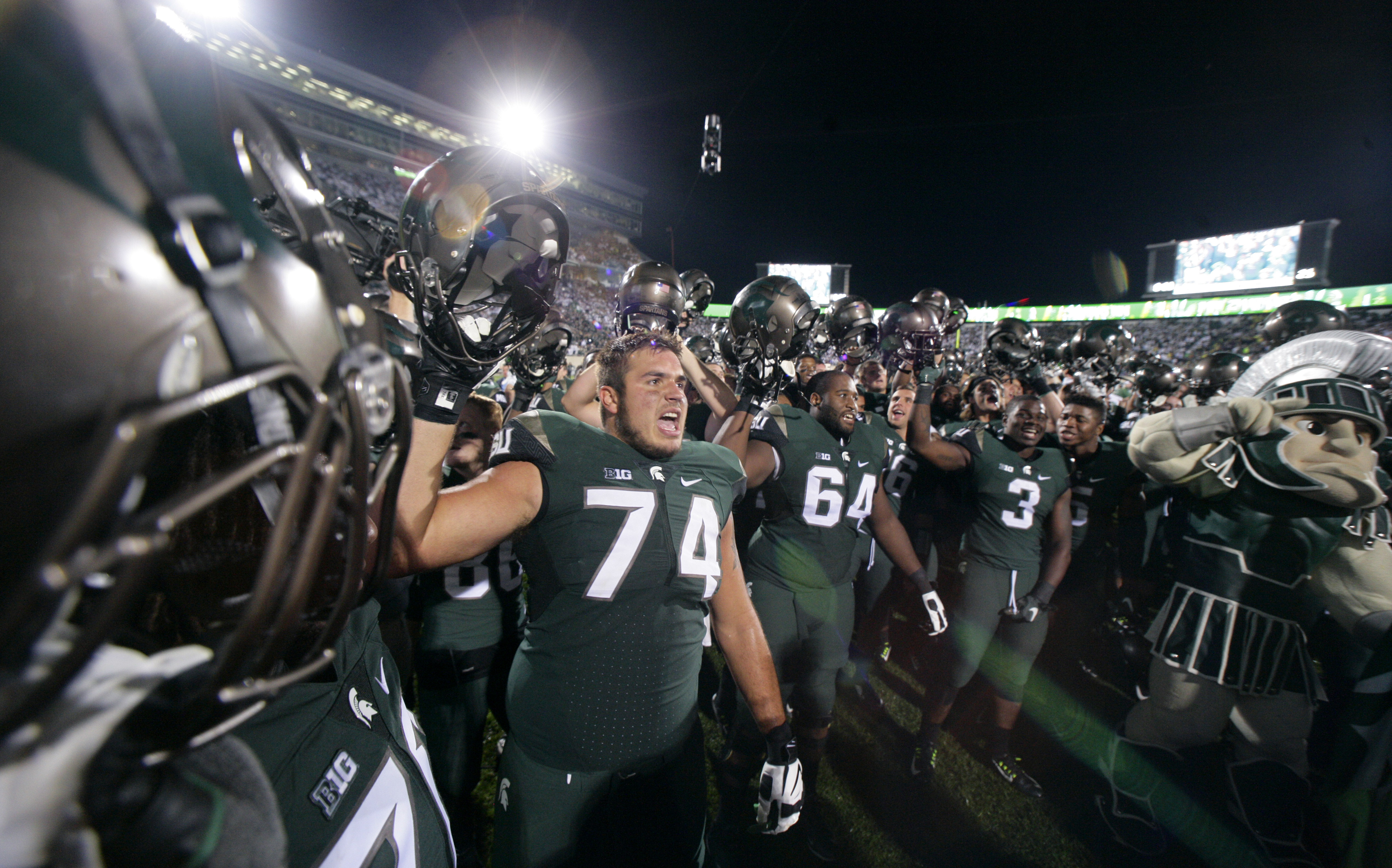 Michigan State players, including Jack Conklin (74), Brandon Clemons (64) and L.J. Scott (3), celebrate following a 31-28 win over Oregon in an NCAA college football game, Saturday, Sept. 12, 2015, in East Lansing, Mich. (AP Photo/Al Goldis)