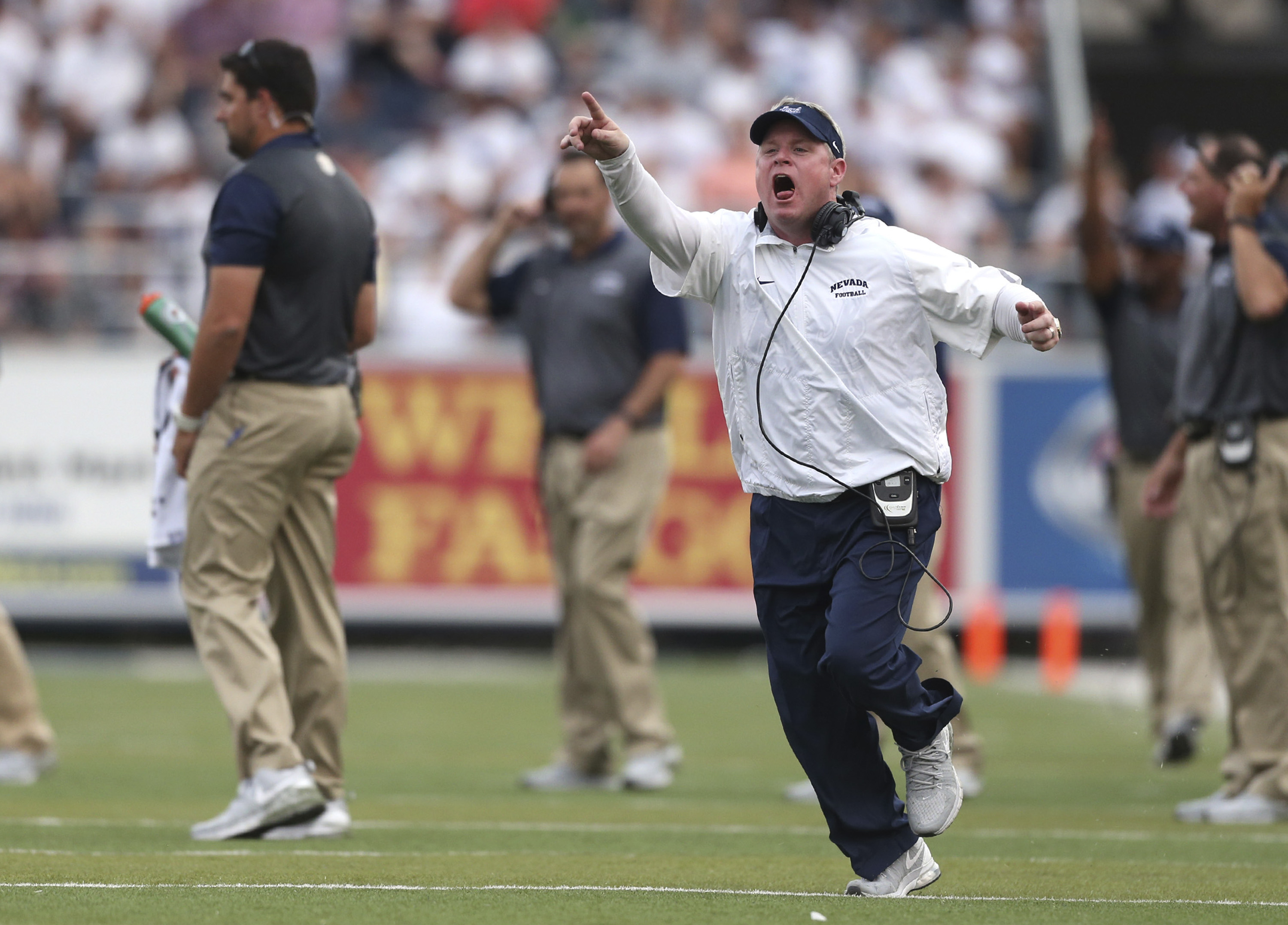 In this Saturday, Sept. 12, 2015, photo, Nevada coach Brian Polian yells to an official during an NCAA college football game against Arizona in Reno, Nev. The Mountain West Conference has fined Polian $10,000 after he twice was called for unsportsmanlike