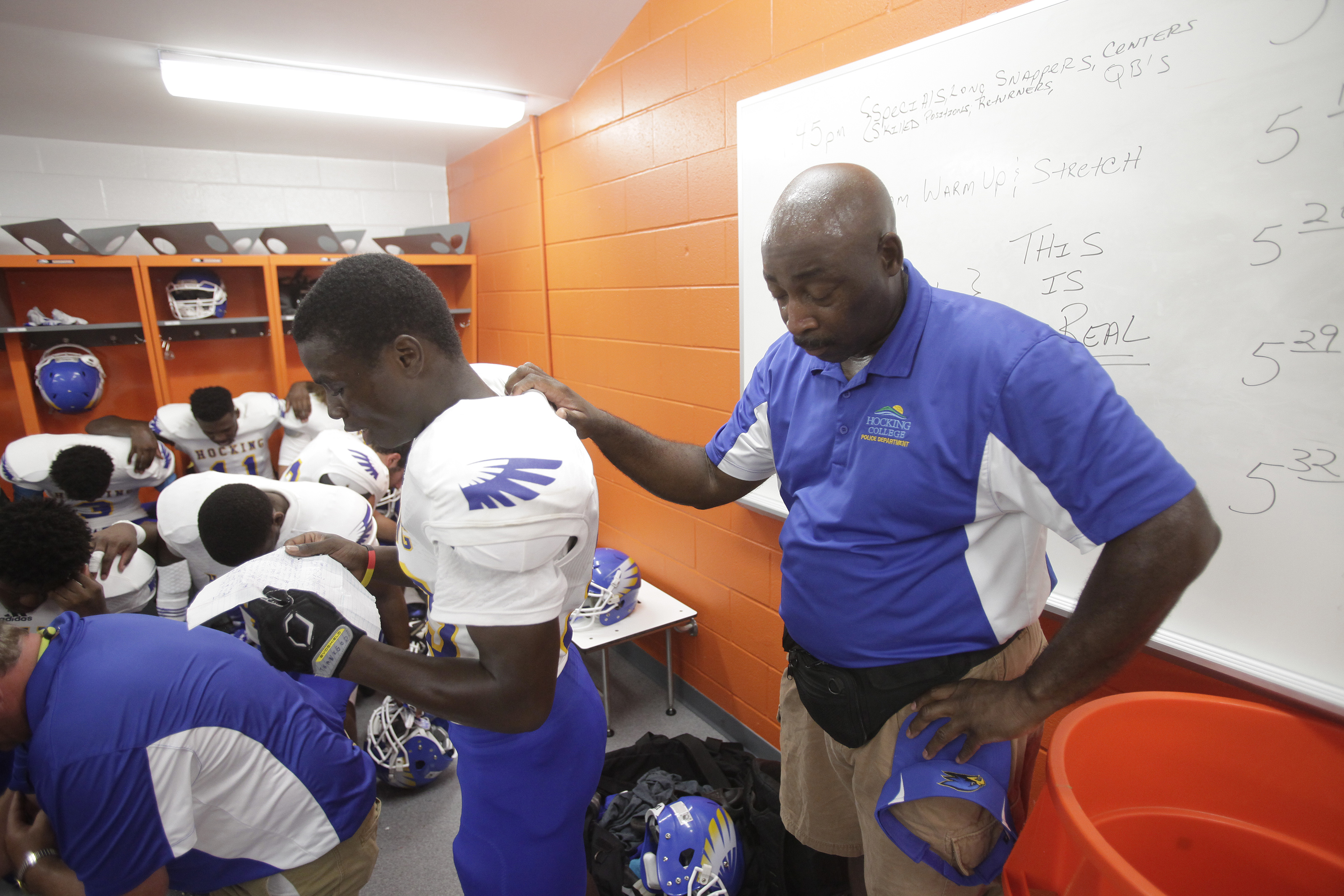 Hocking College head football coach Al Matthews, right, pauses while Drew Milbrooks reads a prayer before the start of the schools first football game, Monday, Aug. 31, 2015, against Ohio Northern University in Ada, Ohio. With falling enrollment and a fin