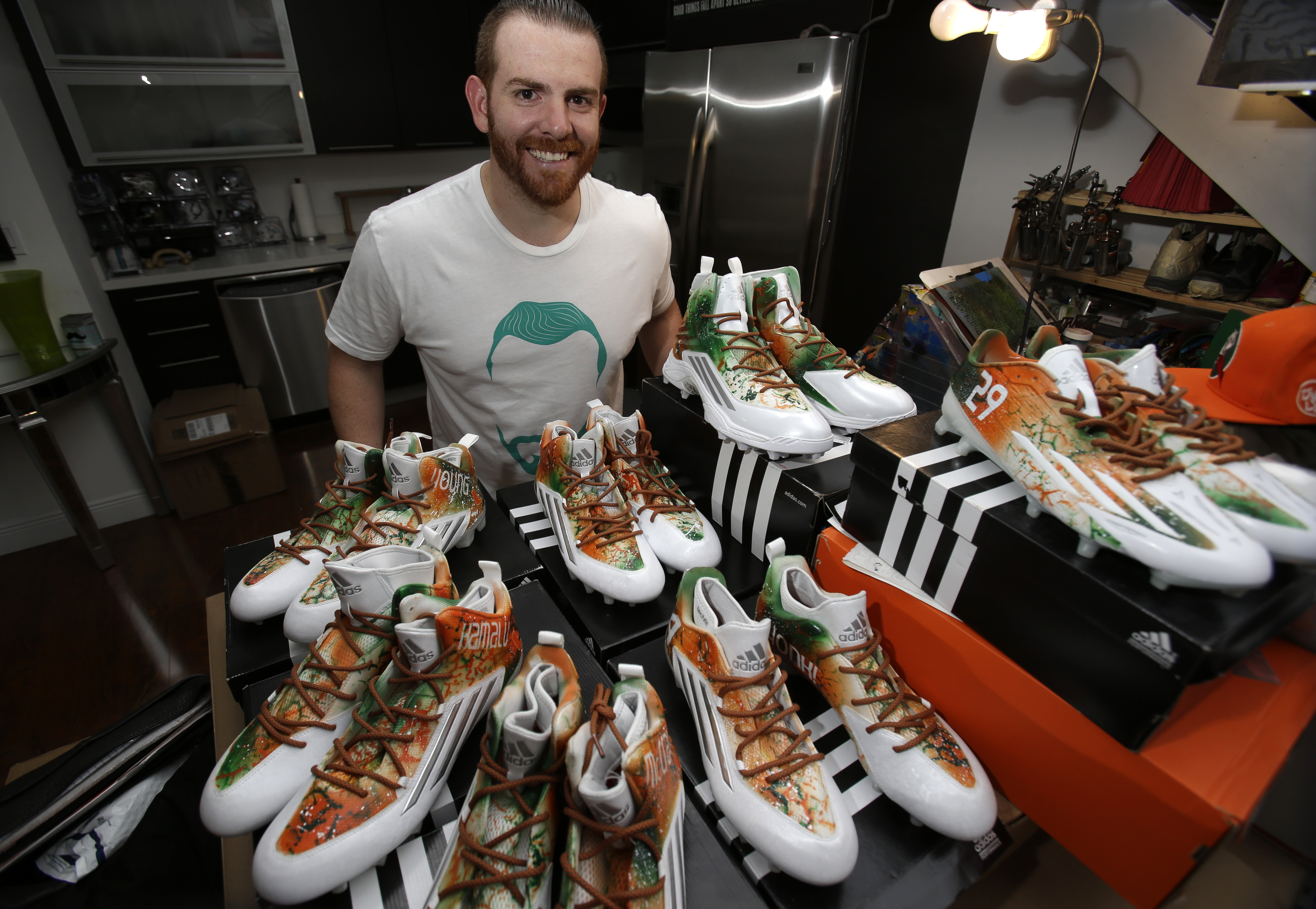 In this photo taken Tuesday, Sept. 15, 2015, Marcus Rivero poses with some of the cleats he painted for Miami football players at his home in Miami. Rivero put in about 400 hours painting about 120 pair of customized cleats that Miami will wear for Saturd
