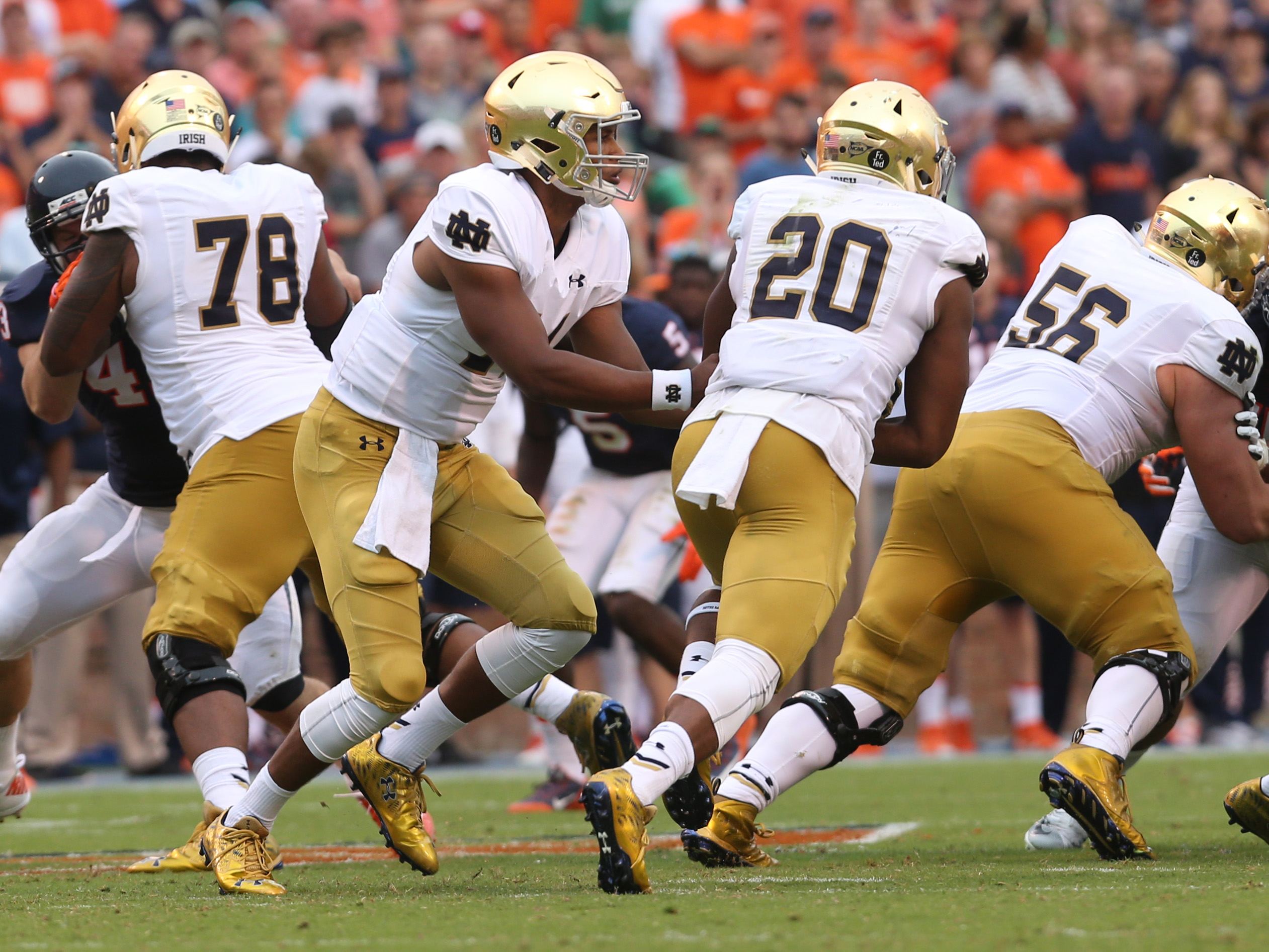 In this photo taken Saturday, Sept. 12, 2015, Notre Dame quarterback DeShone Kizer (14) hands off the ball to running back C.J. Prosise (20) during an NCAA football game against Virginia in Charlottesville, Va. Kizer didn't impress Notre Dame at first. Th
