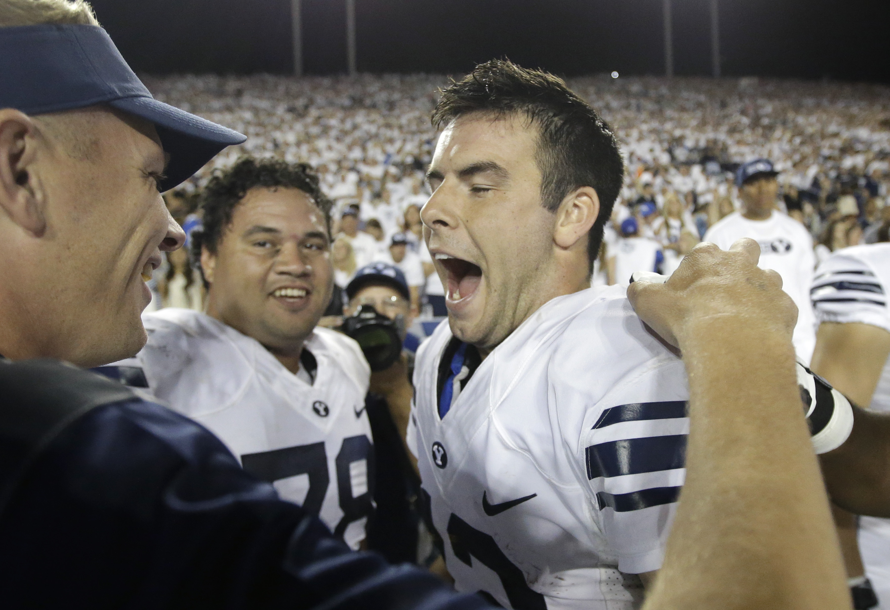 FILE - In this Saturday, Sept. 12, 2015, file photo, BYU quarterback Tanner Mangum, right, celebrates on the sidelines in the second half of an NCAA college football game against Boise State in Provo, Utah. No. 19 BYU's game against No. 10 UCLA at the Ros