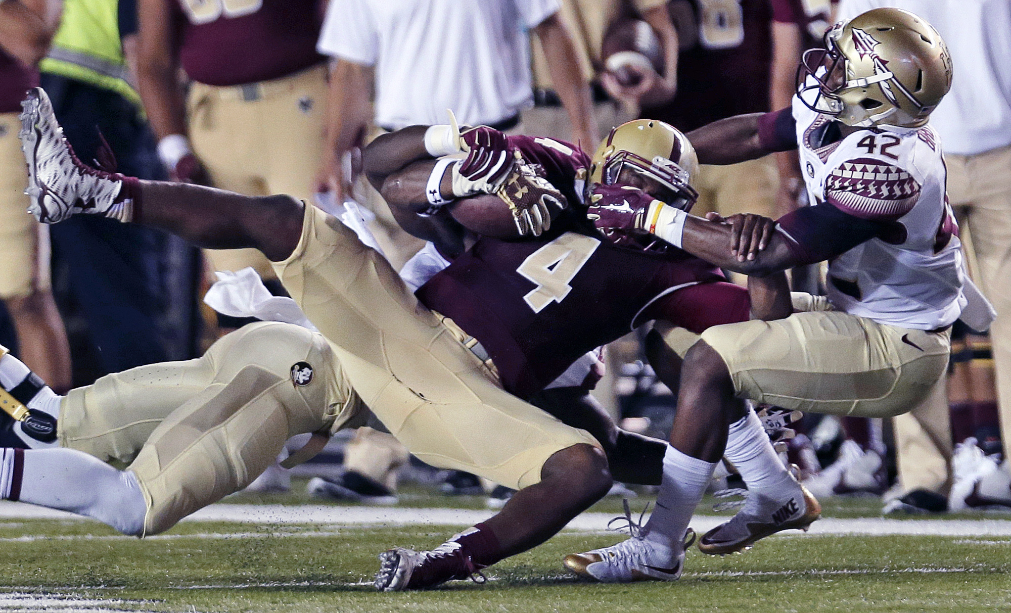 Boston College quarterback Darius Wade (4) is taken down by Florida State defensive back Lamarcus Brutus (42) during the first half of an NCAA college football game in Boston, Friday, Sept. 18, 2015. (AP Photo/Charles Krupa)