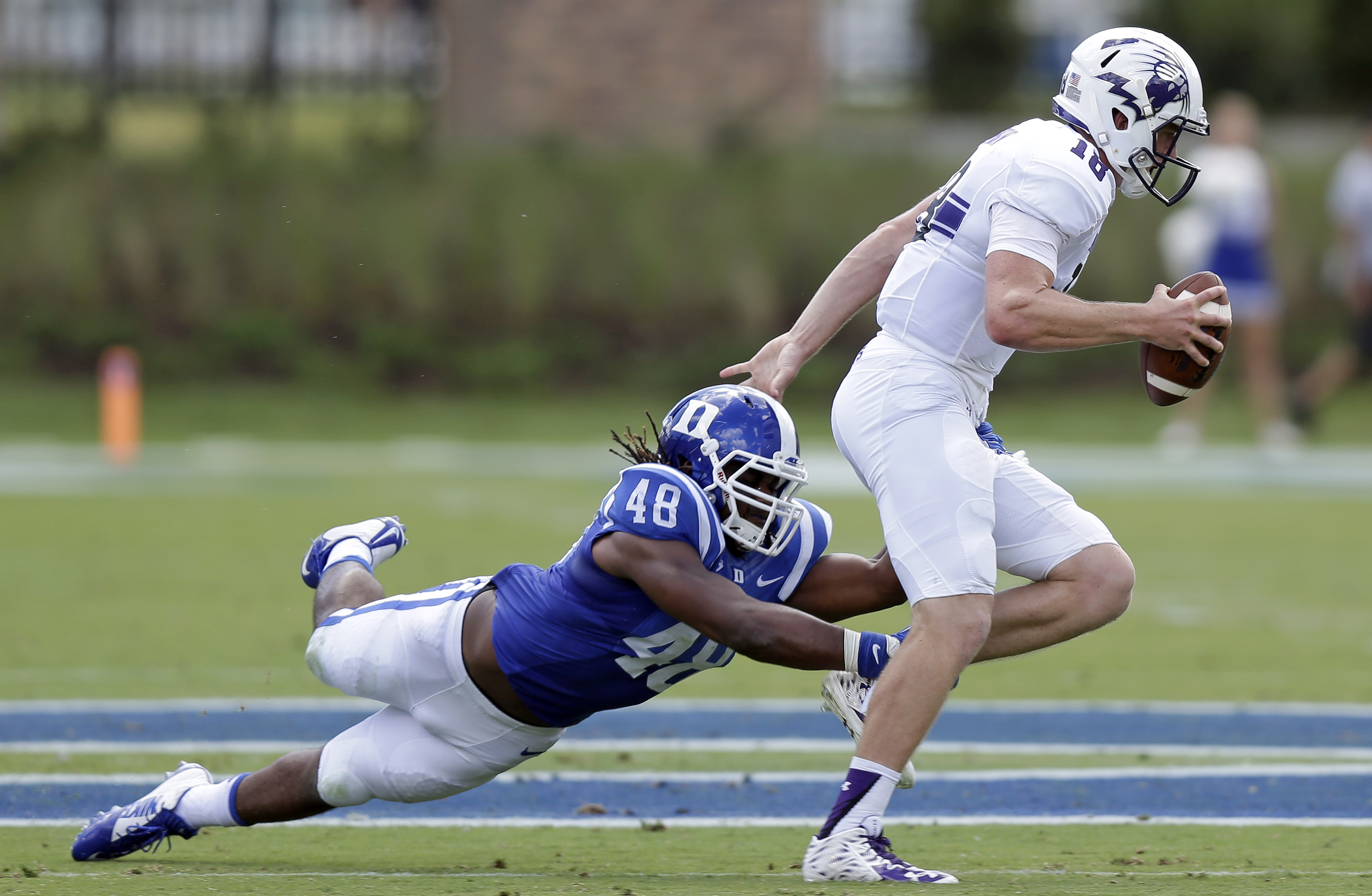 Duke's Deion Williams (48) reaches to tackle Northwestern quarterback Clayton Thorson (18) during the first half of an NCAA college football game in Durham, N.C., Saturday, Sept. 19, 2015. (AP Photo/Gerry Broome)