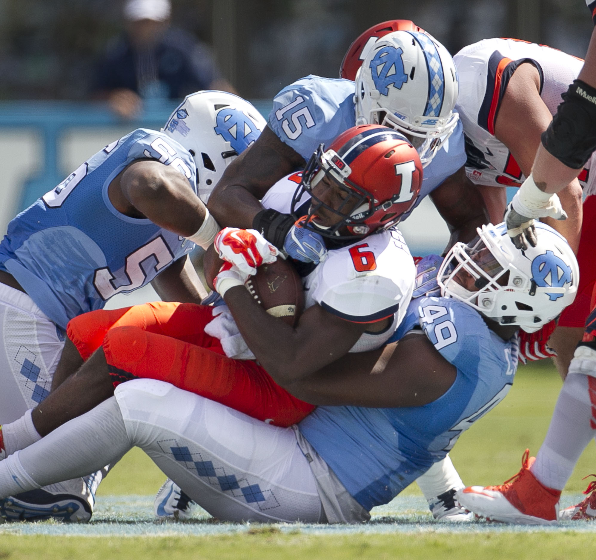 North Carolina's Jeremiah Clarks (49) and Donnie Miles (15) stop Illinois' Josh Ferguson (6) for a loss in the first half of an NCAA football game, Saturday, Sept. 19, 2015 at Kenan Stadium in Chapel Hill, N.C. (Robert Willett/The News & Observer via AP)
