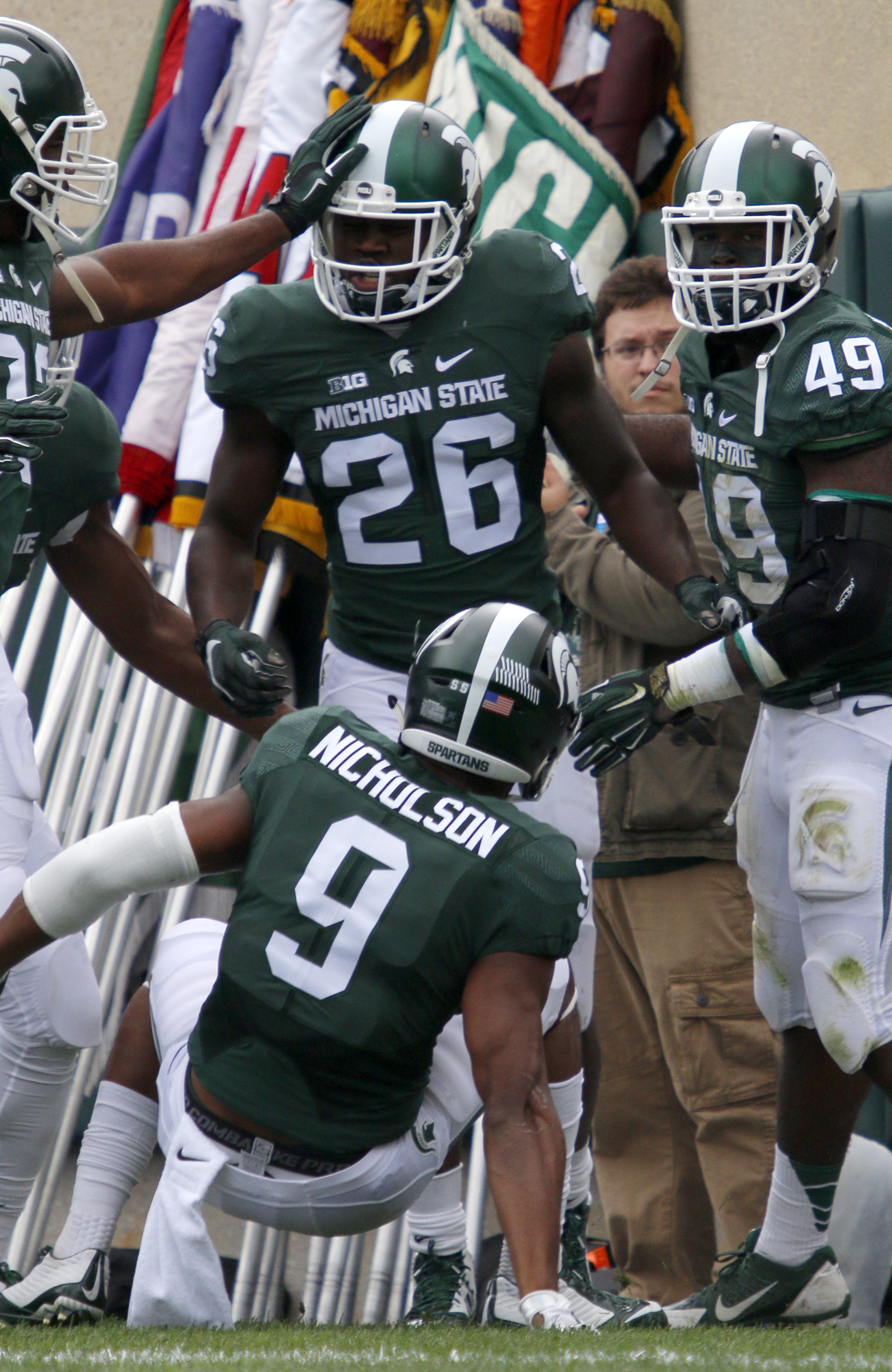 Michigan State's R.J. Williamson (26), Montae Nicholson (9), Shane Jones (49) and Damon Knox, left, celebrate Williamson's interception return for a touchdown against Air Force during the first quarter of an NCAA college football game, Saturday, Sept. 19,
