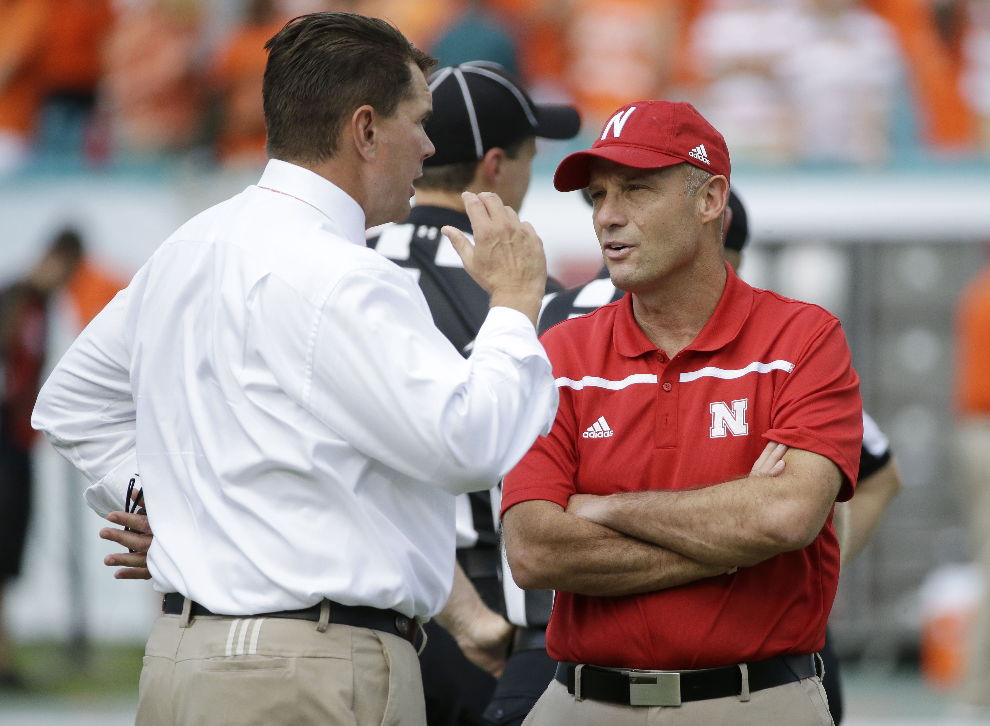 Miami head coach Al Golden, left, and Nebraska head coach Mike Riley talk before the start of an NCAA college football game, Saturday, Sept. 19, 2015 in Miami Gardens, Fla. (AP Photo/Wilfredo Lee)