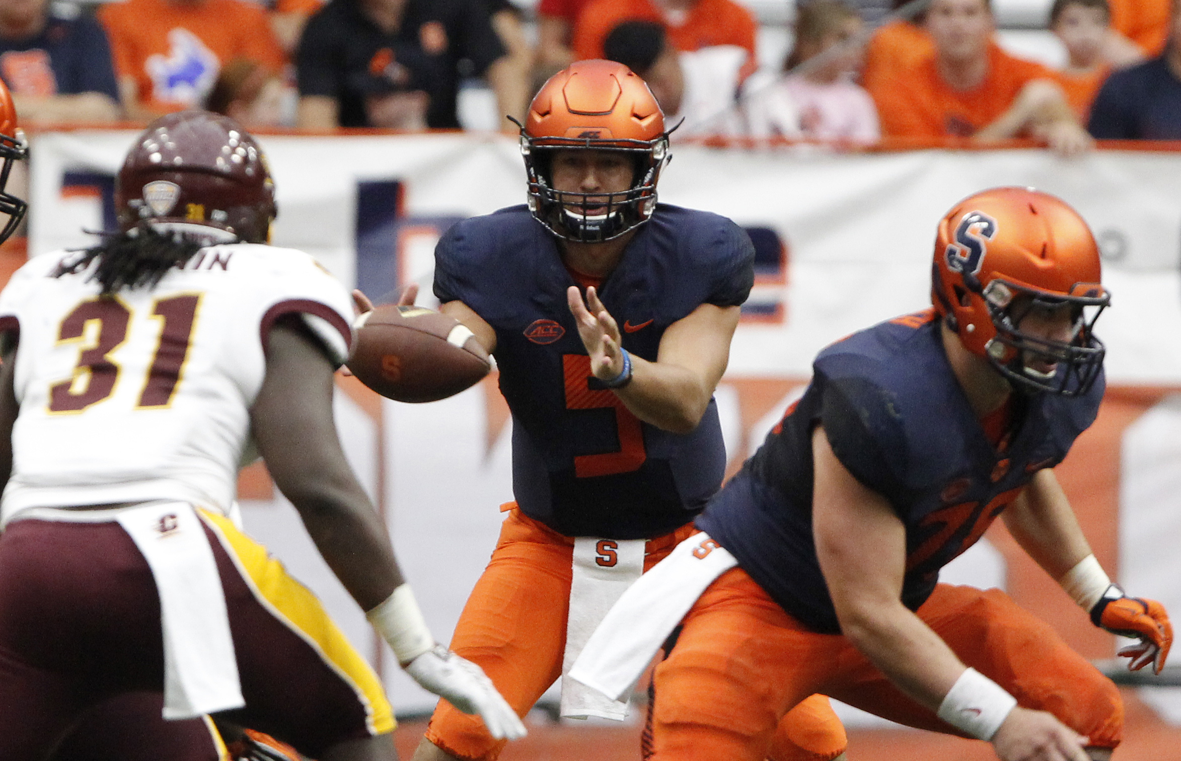 Syracuse's Austin Wilson, center, takes a snap in the second half of an NCAA college football game against Central Michigan in Syracuse, N.Y., Saturday, Sept. 19, 2015. Syracuse won 30  27. (AP Photo/Nick Lisi)