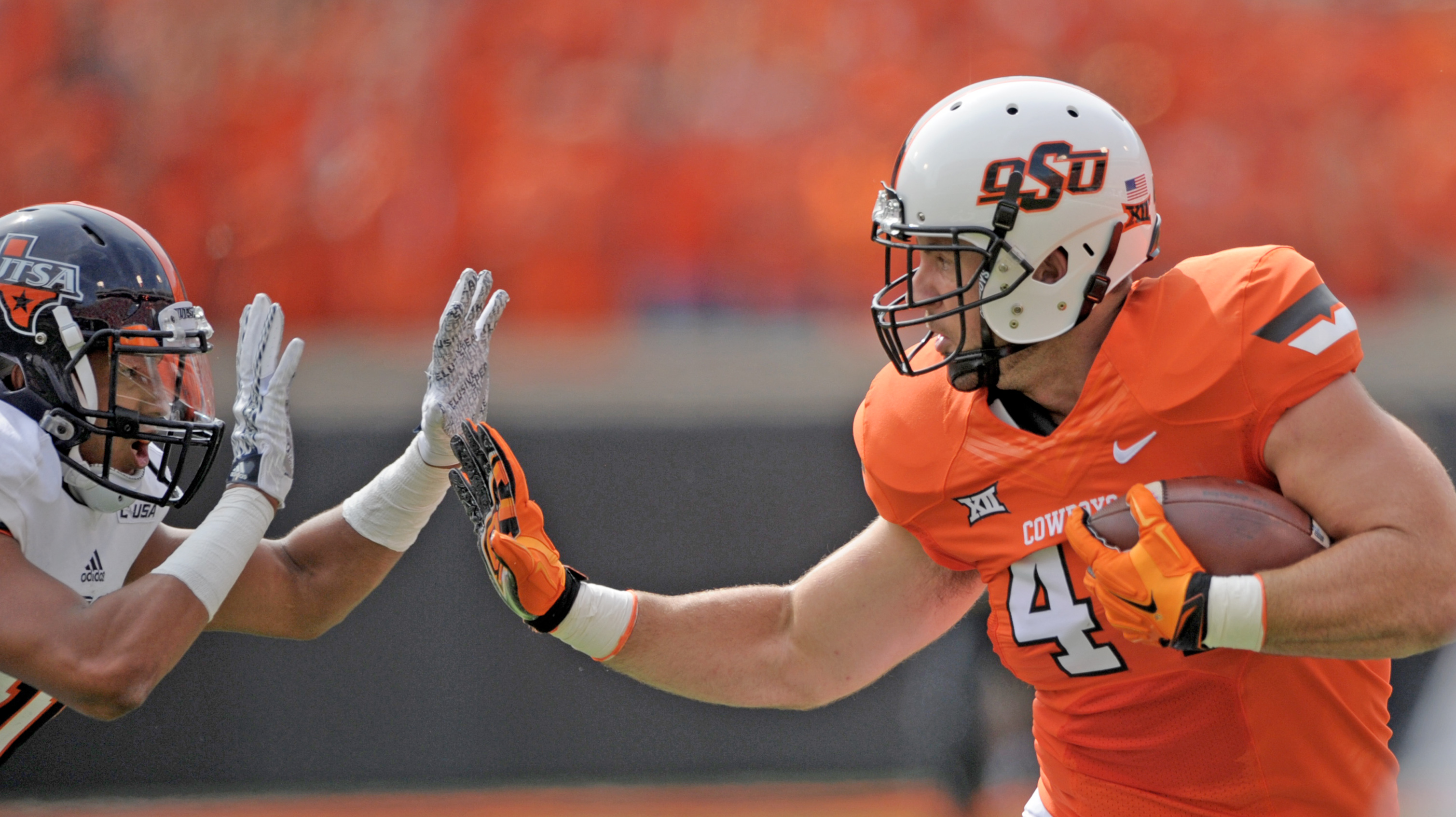 Oklahoma State fullback Jeremy Seaton, right, fends off UTSA safety Nate Gaines for a 45 yard reception during the first quarter of an NCAA college football game in Stillwater, Okla., Saturday, Sept. 19, 2015. (AP Photo/Brody Schmidt)