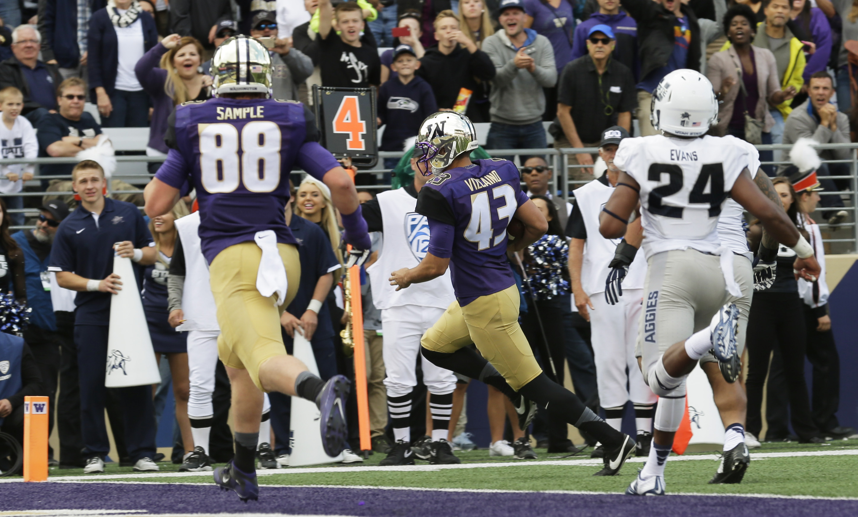 Washington kicker Tristan Vizcaino (43) runs for a touchdown on a fake field goal play as Utah State' Marwin Evans (24) pursues and Washington's Drew Sample (88) watches in the first half of an NCAA college football game, Saturday, Sept. 19, 2015, in Seat