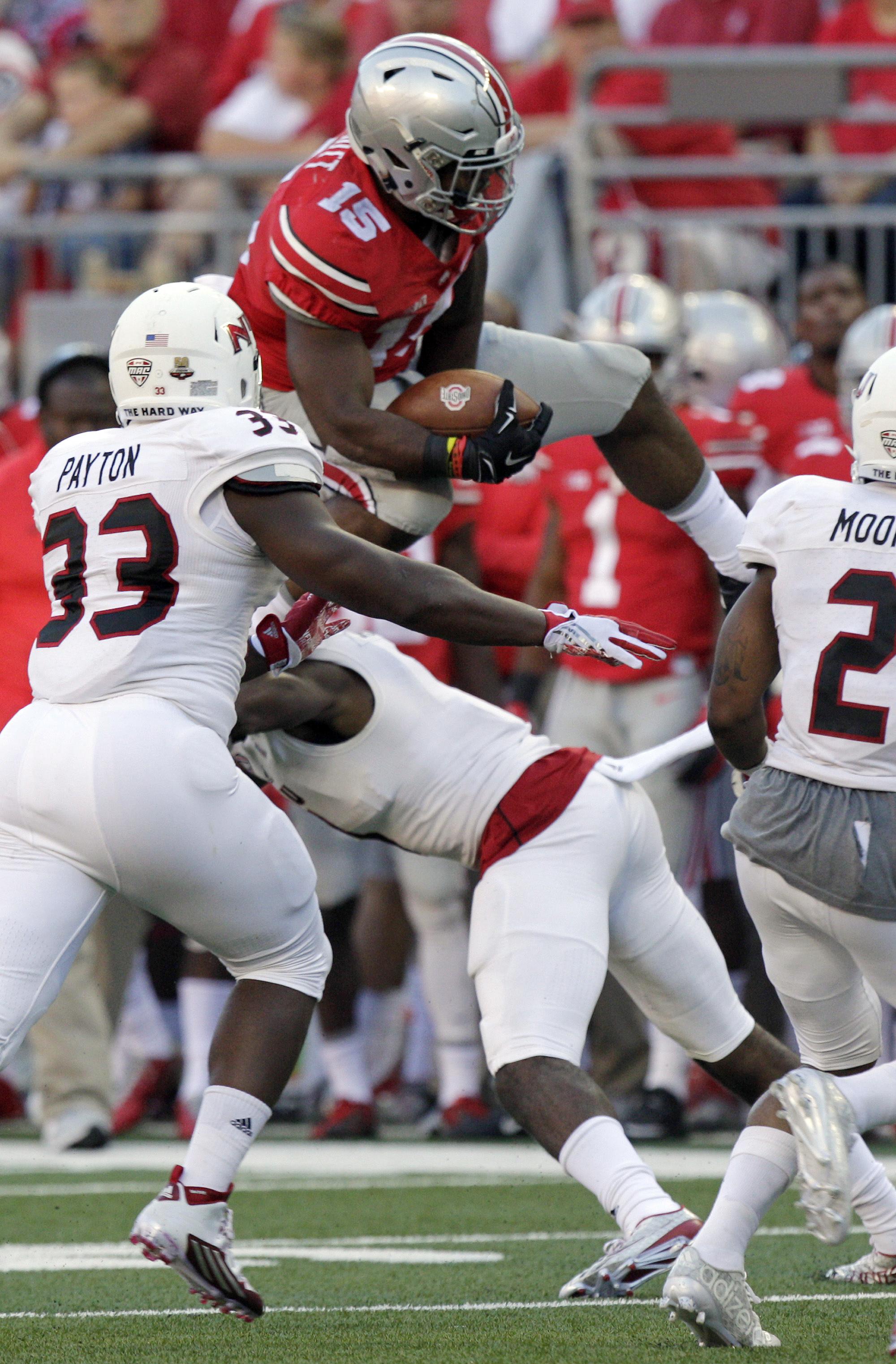 Ohio State running back Ezekiel Elliott, top, leaps over Northern Illinois cornerback Albert Smalls during the third quarter of an NCAA college football game Saturday, Sept. 19, 2015, in Columbus, Ohio. Ohio State won 20-13. (AP Photo/Jay LaPrete)