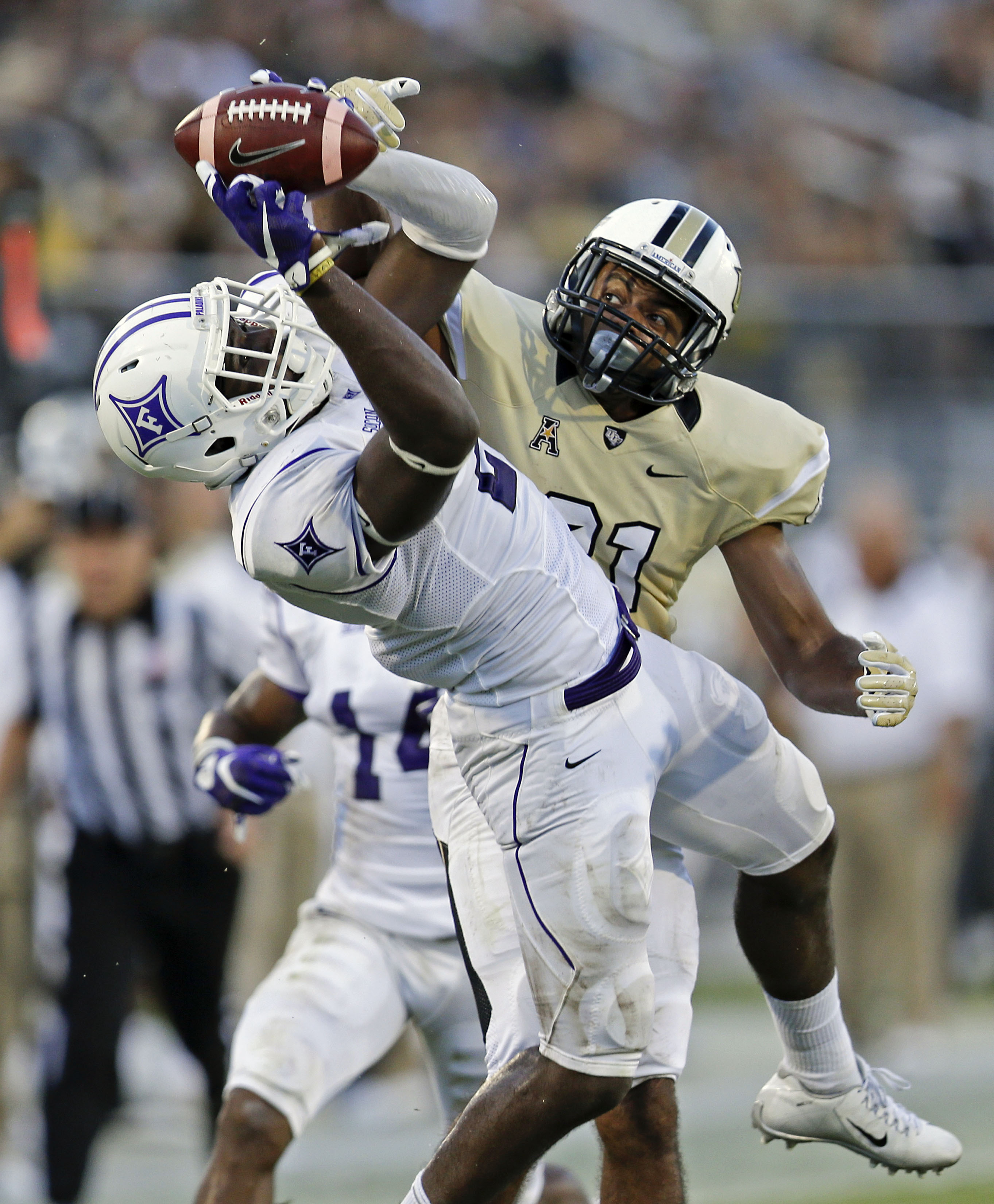 Furman safety Trey Robinson, left, intercepts a pass intended for Central Florida wide receiver Chris Johnson, right, during the first half an NCAA college football game, Saturday, Sept. 19, 2015, in Orlando, Fla. (AP Photo/John Raoux)