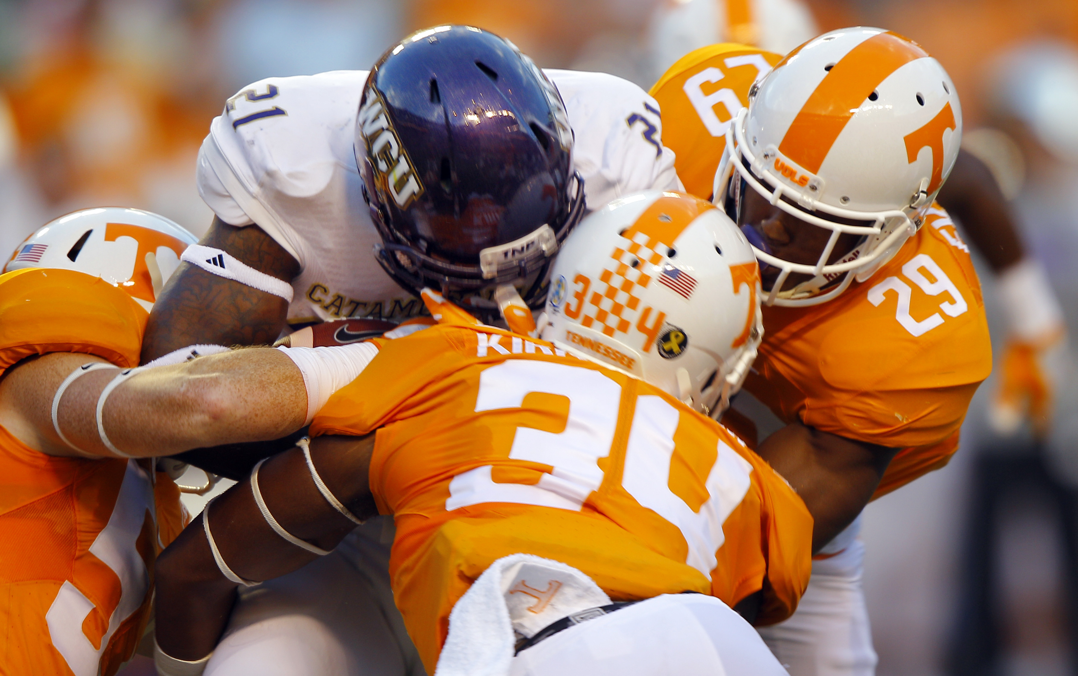 Western Carolina running back Detrez Newsome (21) is tackled by Tennessee linebacker Darrin Kirkland Jr. (34), defensive back Evan Berry (29) and defensive lineman Kyle Phillips (5) during the first half of an NCAA college football game Saturday, Sept. 19