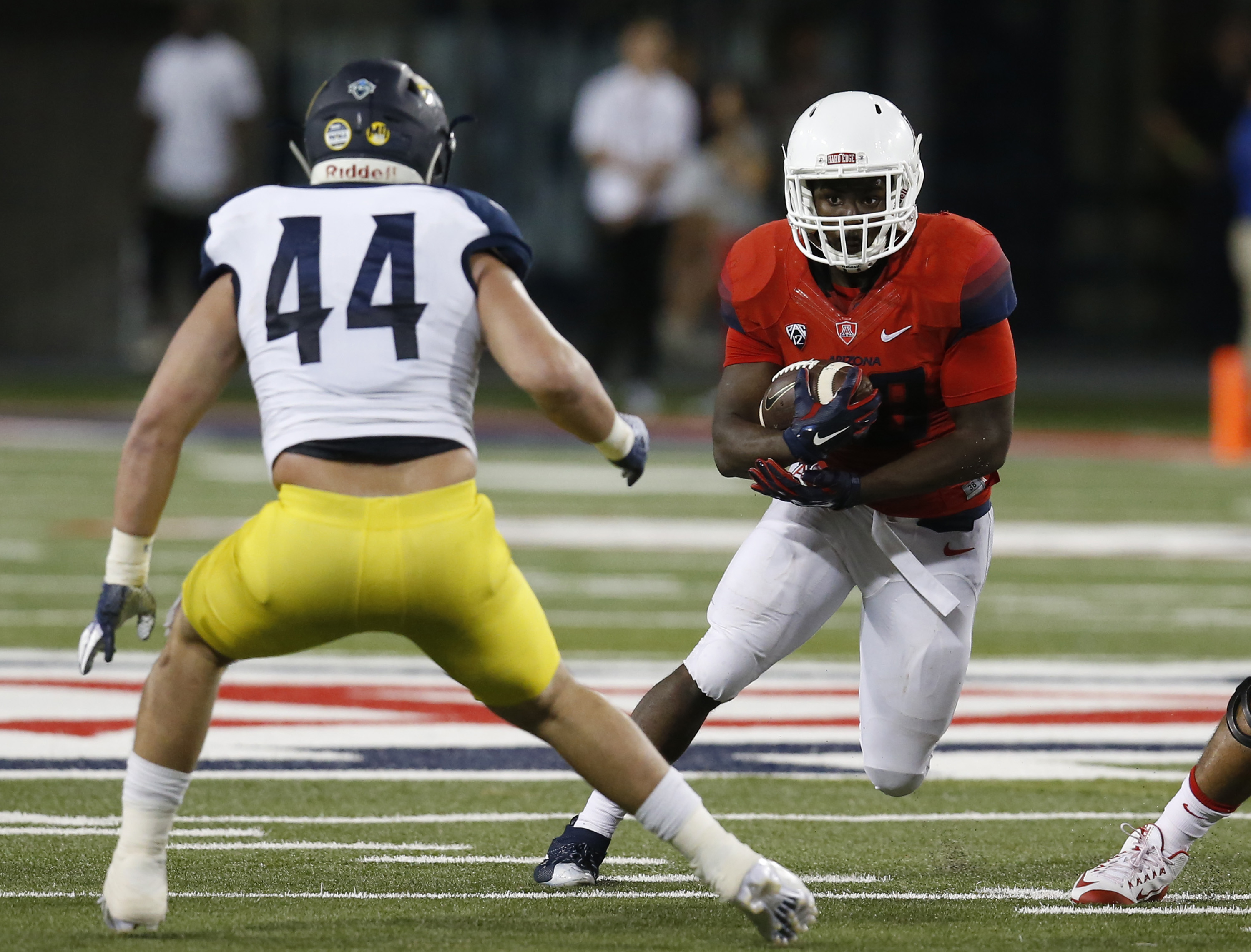 Arizona running back Nick Wilson carries for a first down in front of Northern Arizona linebacker Jake Thomas (44) during the first half of an NCAA college football game, Saturday, Sept. 19, 2015, in Tucson, Ariz. (AP Photo/Rick Scuteri)