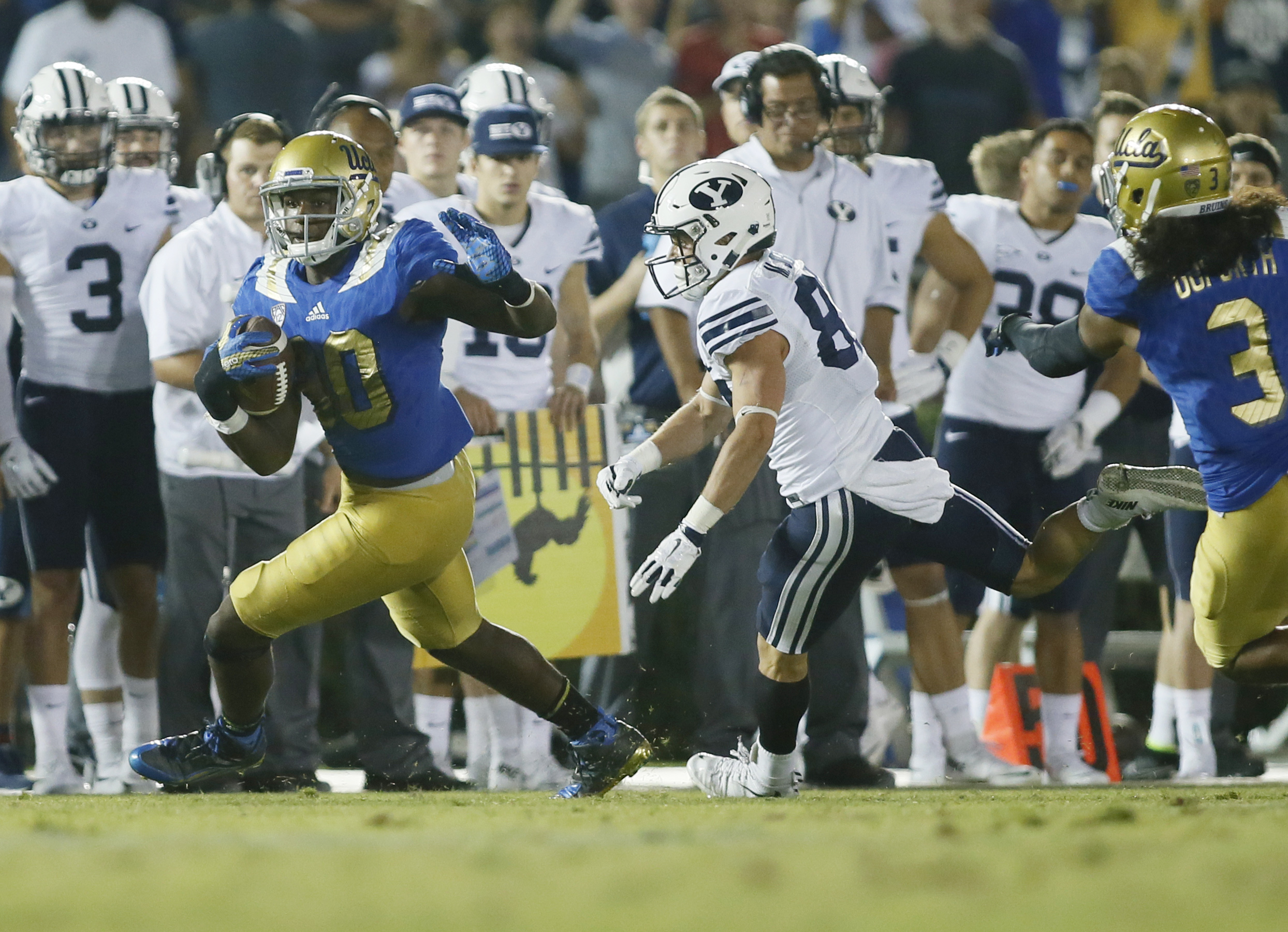 UCLA linebacker Myles Jack runs with the ball after intercepting the ball while BYU wide receiver Mitchell Juergens runs after him late in the fourth quarter of an NCAA college football game, Saturday, Sept. 19, 2015, in Pasadena, Calif. UCLA won 24-23. (