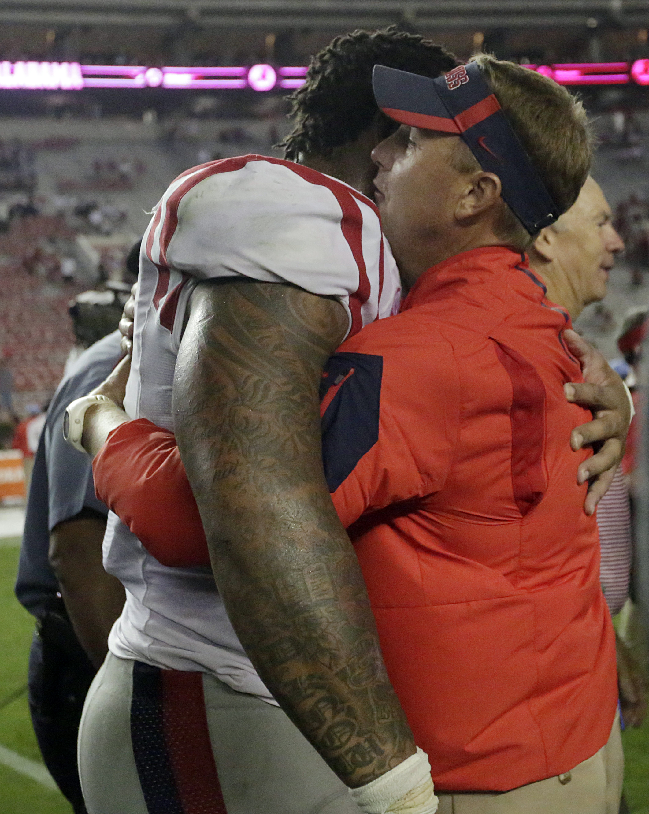 Mississippi defensive tackle Robert Nkemdiche, left, hugs Mississippi head coach Hugh Freeze after a win against Alabama after an NCAA college football game, Sunday, Sept. 20, 2015, in Tuscaloosa, Ala. Mississippi won 43-37. (AP Photo/Brynn Anderson)