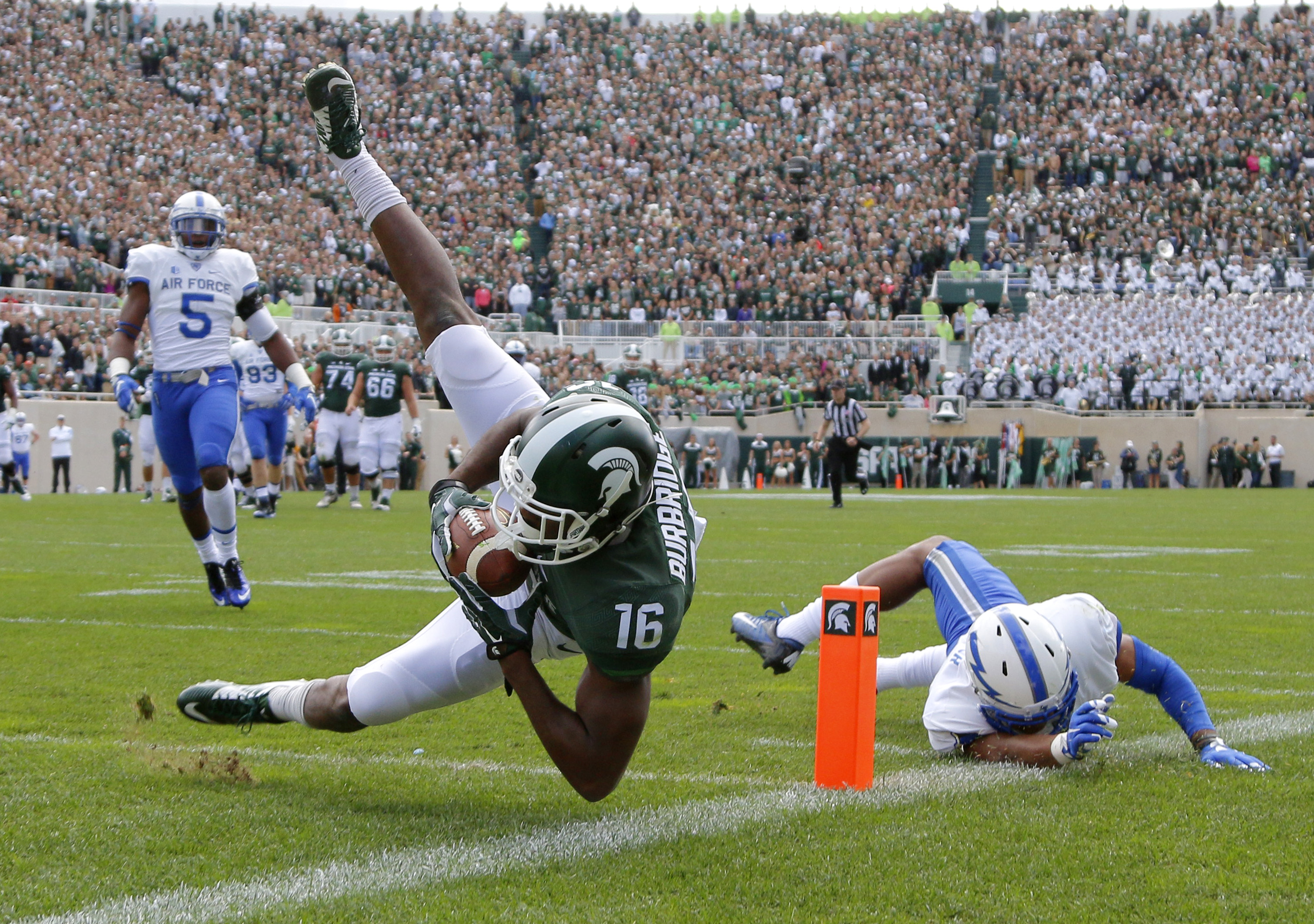 FILE - In this Saturday, Sept. 19, 2015, file photo, Michigan State's Aaron Burbridge (16) comes down with a reception for a touchdown against Air Force's Kalon Baker, right, and Dexter Walker (5) during an NCAA college football game in East Lansing, Mich