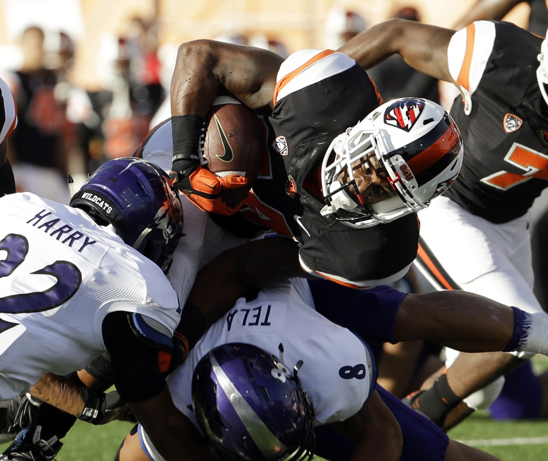 FILE - In this Sept. 4, 2015, file photo, Oregon State running back Storm Woods, top, carries against Weber State cornerback Xequille Harry (22) and Emmett Tela (8) during the first half of an NCAA college football game in Corvallis, Ore. Woods came alive
