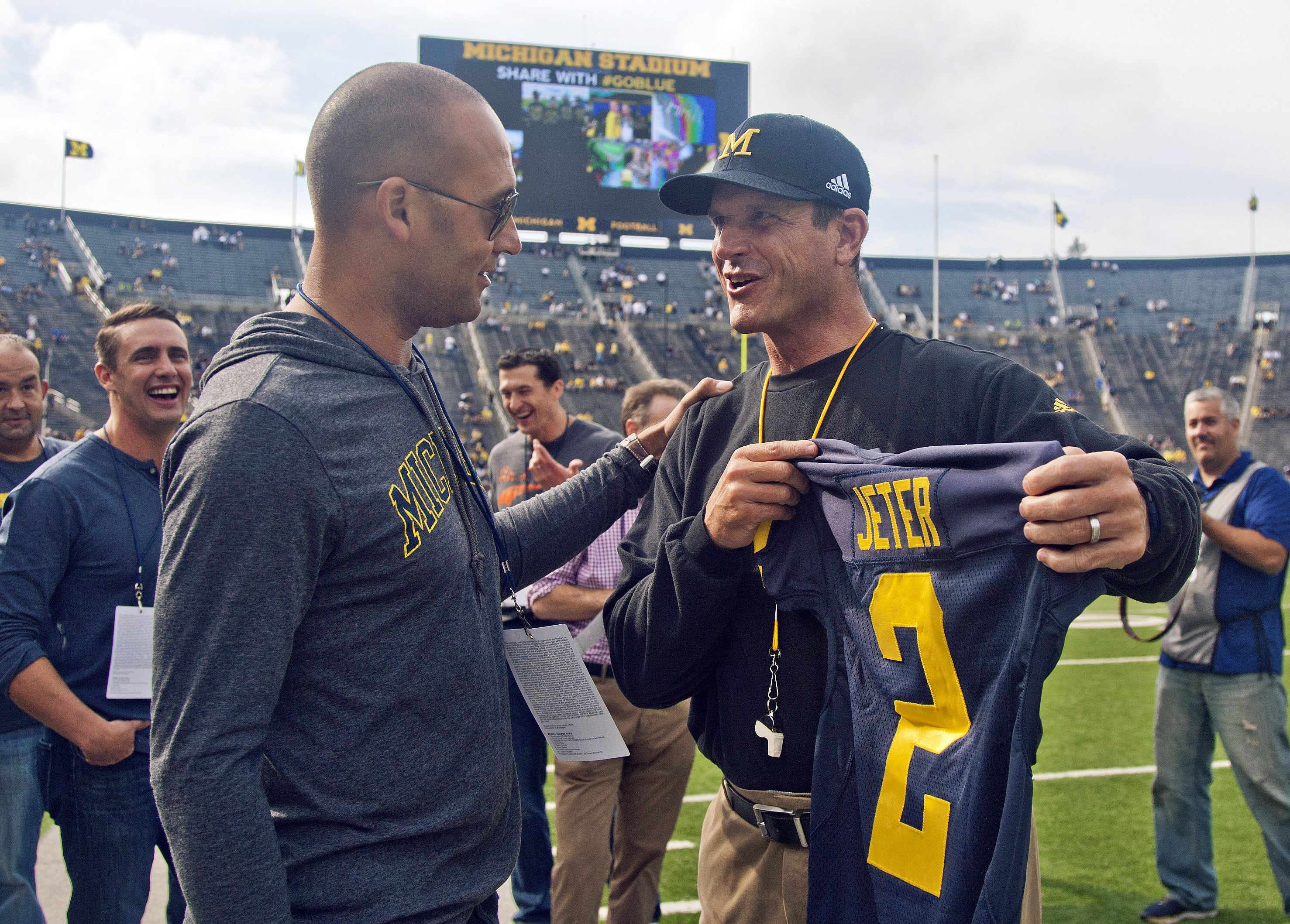 Former New York Yankees baseball player Derek Jeter, left, receives a jersey with his name an No, 2 from Michigan head coach Jim Harbaugh, right, before Michgan's NCAA college football game against BYU in Ann Arbor, Mich., Saturday, Sept. 26, 2015. Jeter