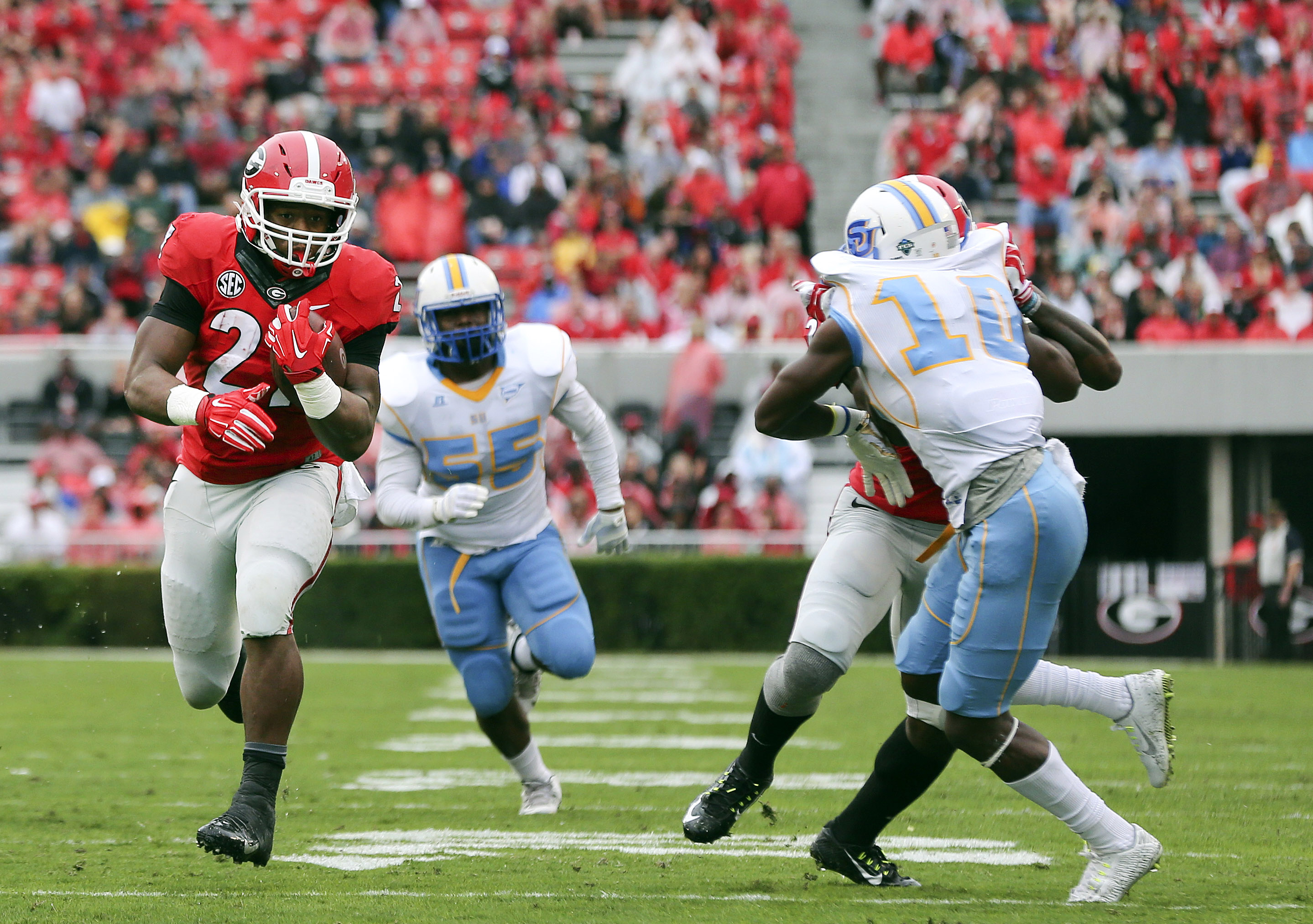 Georgia running back Nick Chubb (27) runs away from Southern's Kentavious Preston (55) and  Danny Johnson (10) for a touchdown in the first half of an NCAA college football game  Saturday, Sept. 26, 2015, in Athens , Ga. (AP Photo/John Bazemore)