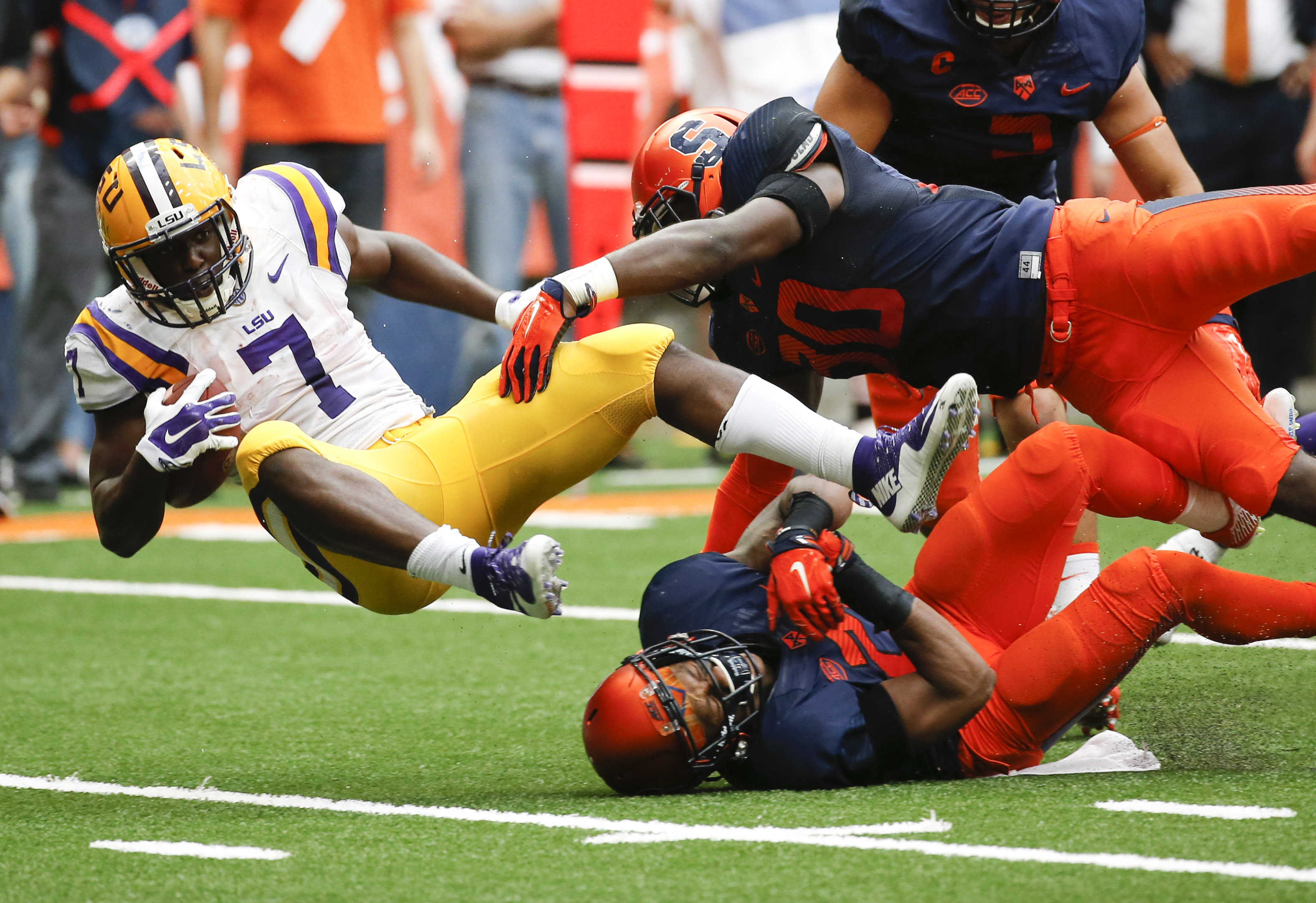 LSU running back Leonard Fournette (7) is tackled by Syracuse defenders Parris Bennett (30) and Chauncey Scissum (21) during the second half of an NCAA college football game on Saturday, Sept. 26, 2015, in Syracuse, N.Y. (AP Photo/Mike Groll)