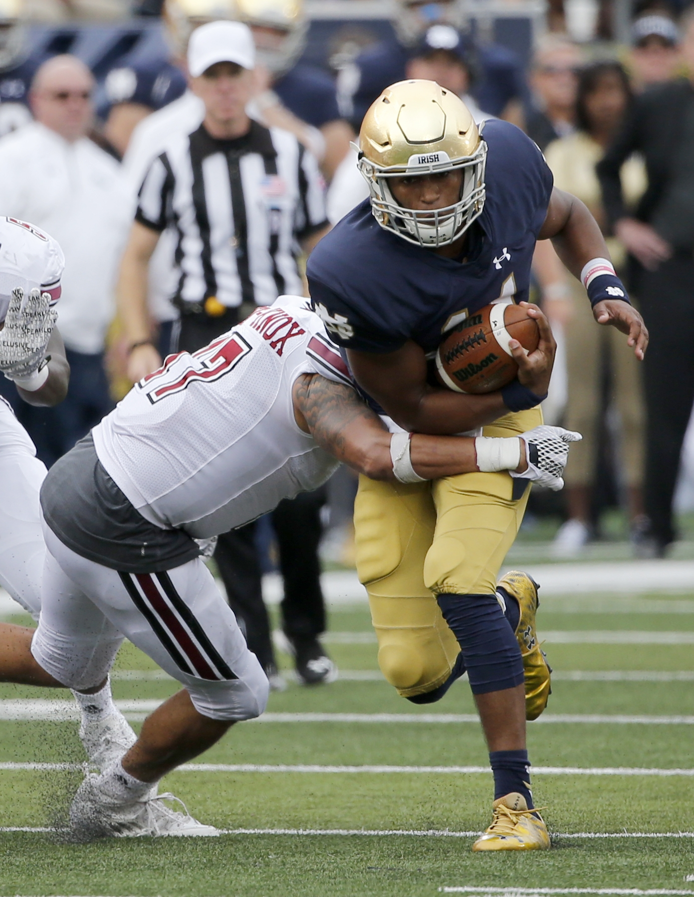 Notre Dame 's DeShone Kizer, right, tries to get past the arm of Massachusetts's Jovan Santos-Knox during the first half of an NCAA college football game Saturday, Sept. 26, 2015, in South Bend, Ind. (AP Photo/Charles Rex Arbogast)