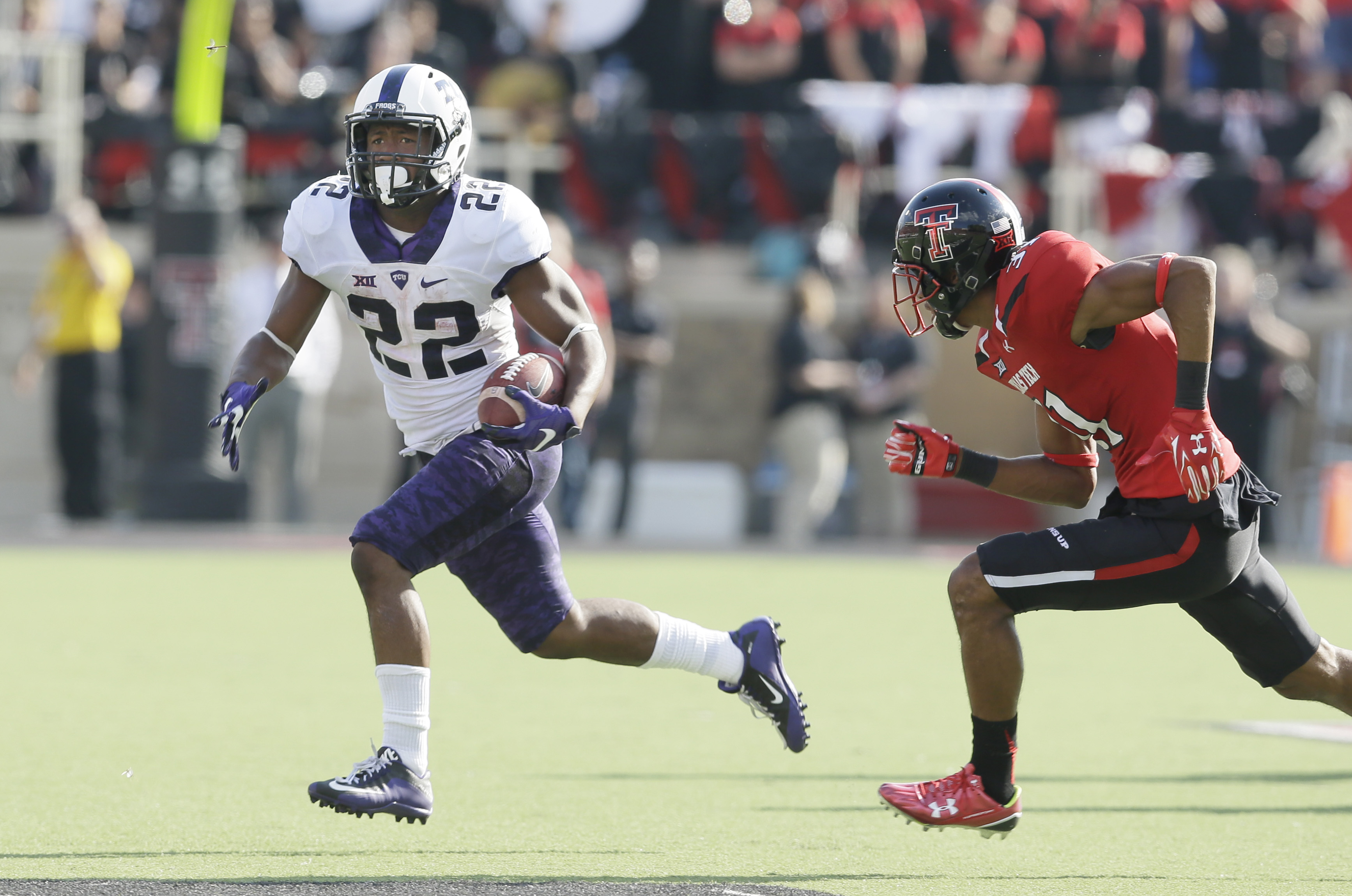 TCU running back Aaron Green (22) finds open field to run against Texas Tech defensive back Justis Nelson (31) during the first half of an NCAA college football game Saturday, Sept. 26, 2015, in Lubbock, Texas. (AP Photo/LM Otero)