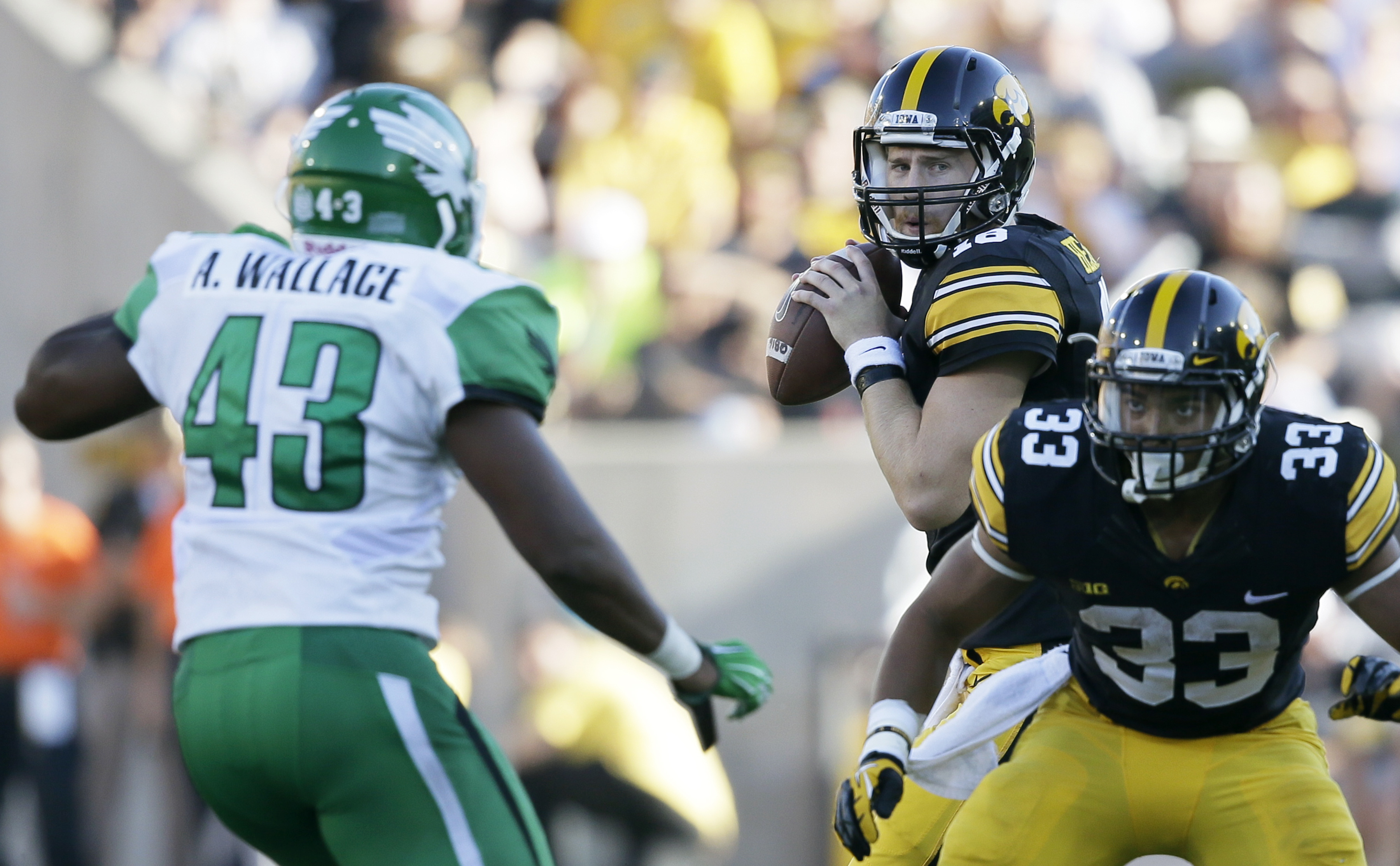 Iowa quarterback C.J. Beathard, center, looks to throw a pass as teammate Jordan Canzeri, right, blocks North Texas linebacker Anthony Wallace (43) during the second half of an NCAA college football game, Saturday, Sept. 26, 2015, in Iowa City, Iowa. Iowa