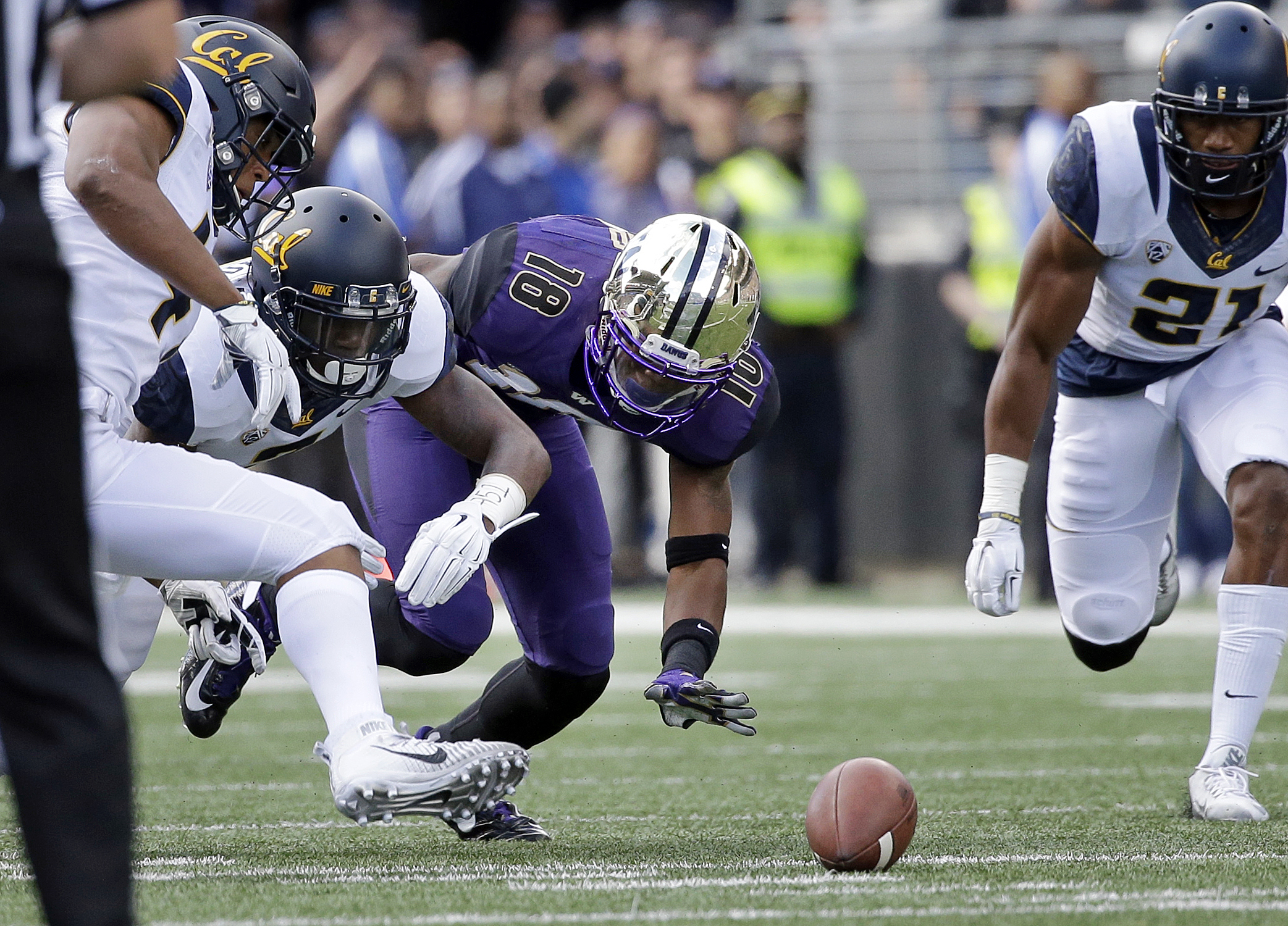 Washington wide receiver Isaiah Renfro (18) watches his fumble as California defenders Hardy Nickerson, left, Darius Allensworth and Stefan McClure (21) surround the ball during the first half an NCAA college football game Saturday, Sept. 26, 2015, in Sea