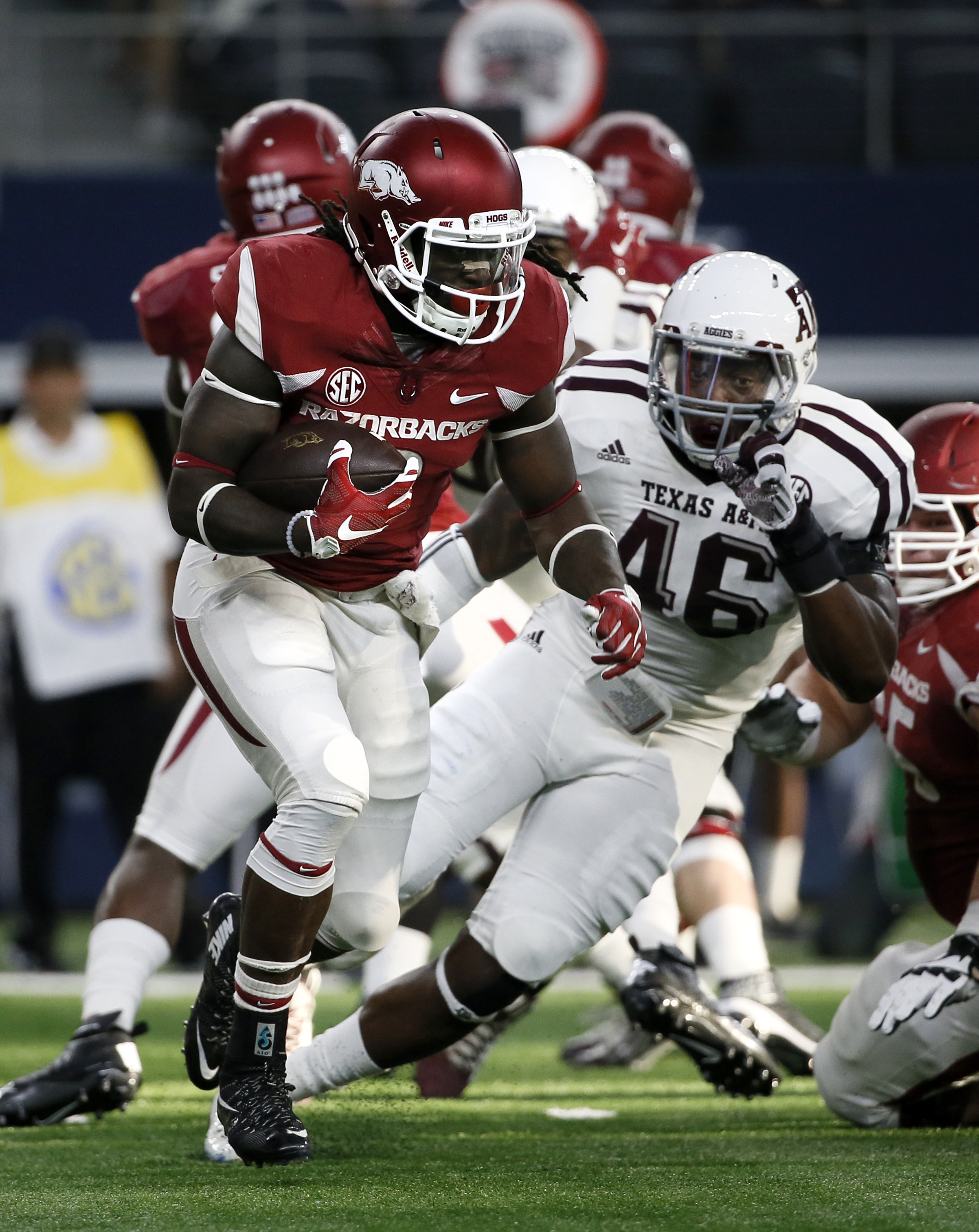 Arkansas running back Alex Collins (3) evades pressure from Texas A&M linebacker A.J. Hilliard (46) during the first half of an NCAA college football game Saturday, Sept. 26, 2015, in Arlington, Texas. (AP Photo/Tony Gutierrez)