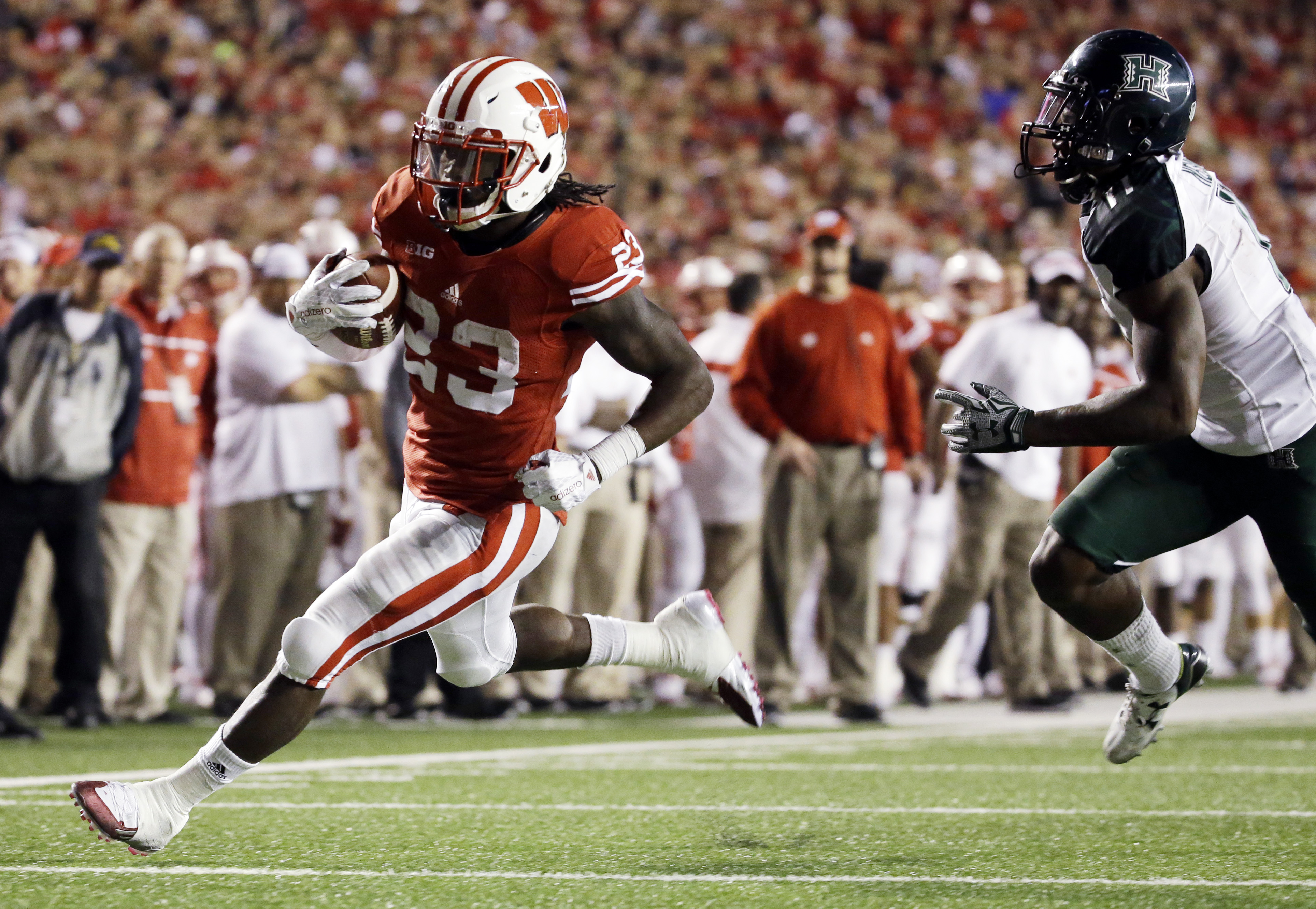 Wisconsin's Dare Ogunbowale gets past Hawaii's Nick Nelson for a touchdown run during the second half of an NCAA college football game Saturday, Sept. 26, 2015, in Madison, Wis. (AP Photo/Morry Gash)