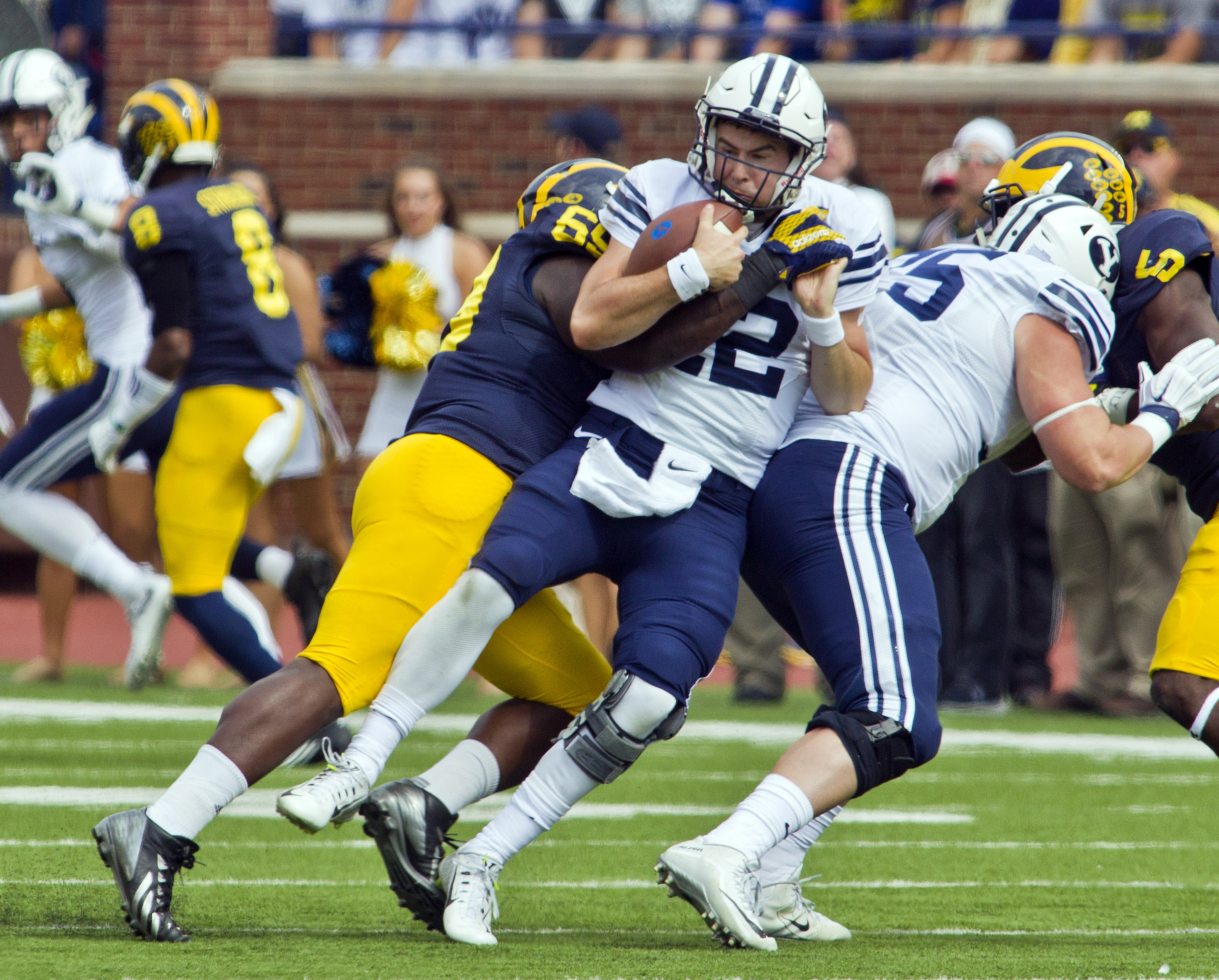 FILE - In this Sept. 26, 2015 file photo, BYU quarterback Tanner Mangum (12) is sacked by Michigan linebacker Noah Furbush (59) in the second quarter of an NCAA college football game in Ann Arbor, Mich.  Michigan is back in The Associated Press poll, rank