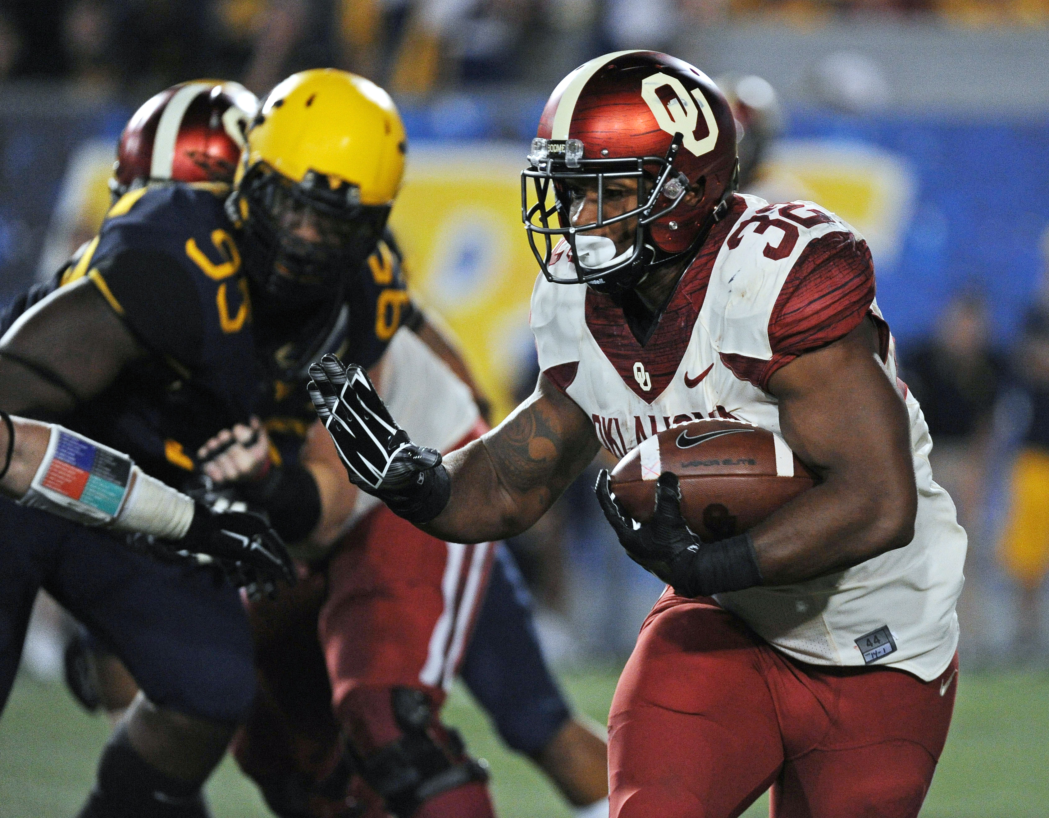 FILE - In this Sept. 20, 2014, file photo, Oklahoma's Samaje Perine (32) reaches to stiff-arm a West Virginia defender during the fourth quarter of an NCAA college football game in Morgantown, W.Va. Oklahoma's Samaje Perine rattles teeth, opens eyes and p