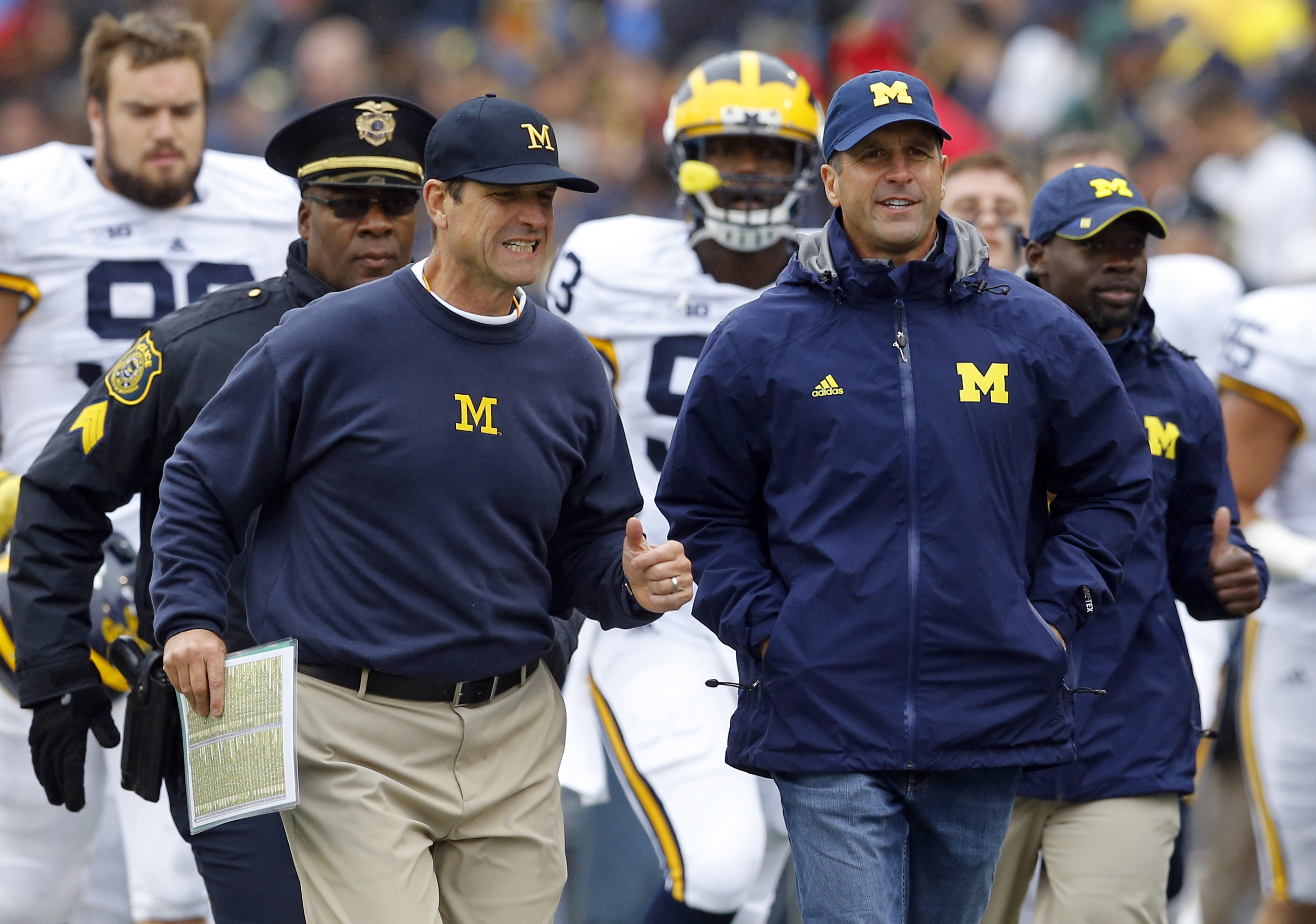 Michigan head coach Jim Harbaugh, left, jogs off the field with his brother, Baltimore Ravens head coach John Harbaugh, at the end of the first half of an NCAA college football game against Maryland, Saturday, Oct. 3, 2015, in College Park, Md. (AP Photo/