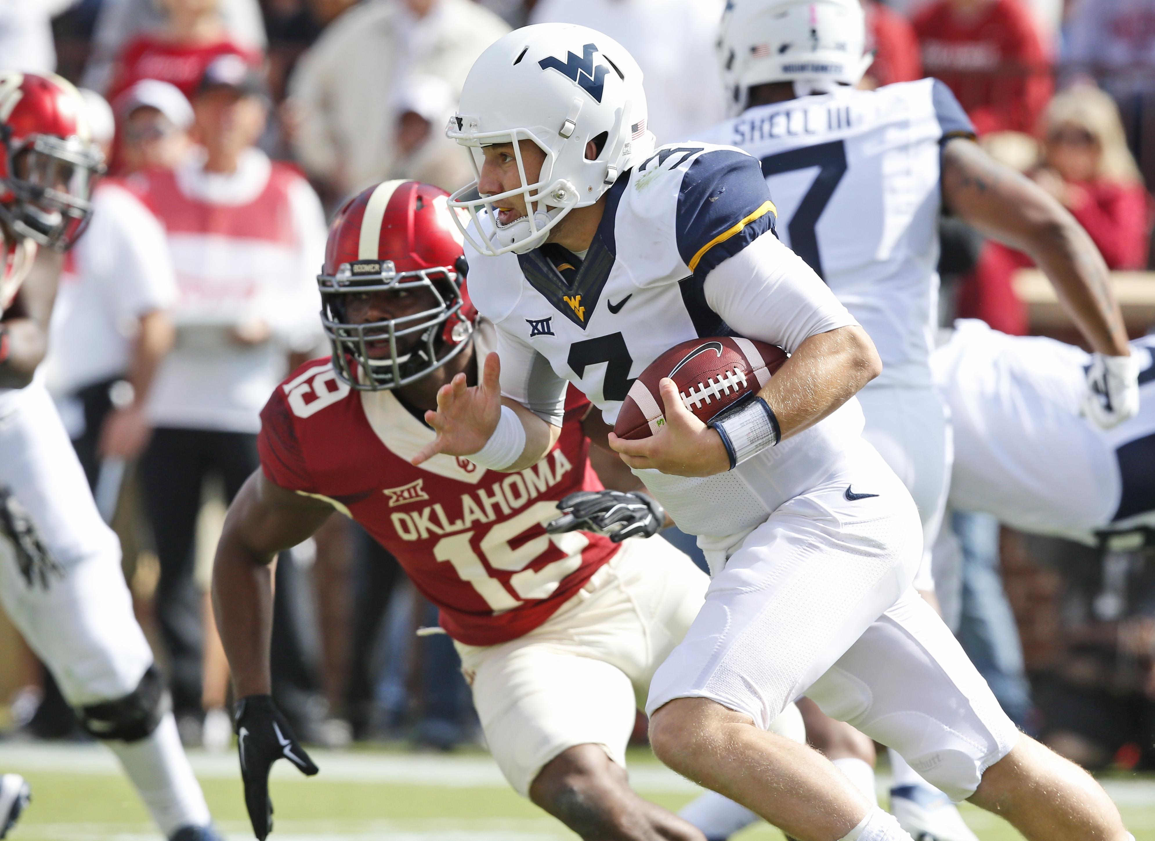 West Virginia quarterback Skyler Howard (3) runs past Oklahoma linebacker Eric Striker (19) in the first quarter of an NCAA college football game in Norman, Okla., Saturday, Oct. 3, 2015. (AP Photo/Sue Ogrocki)