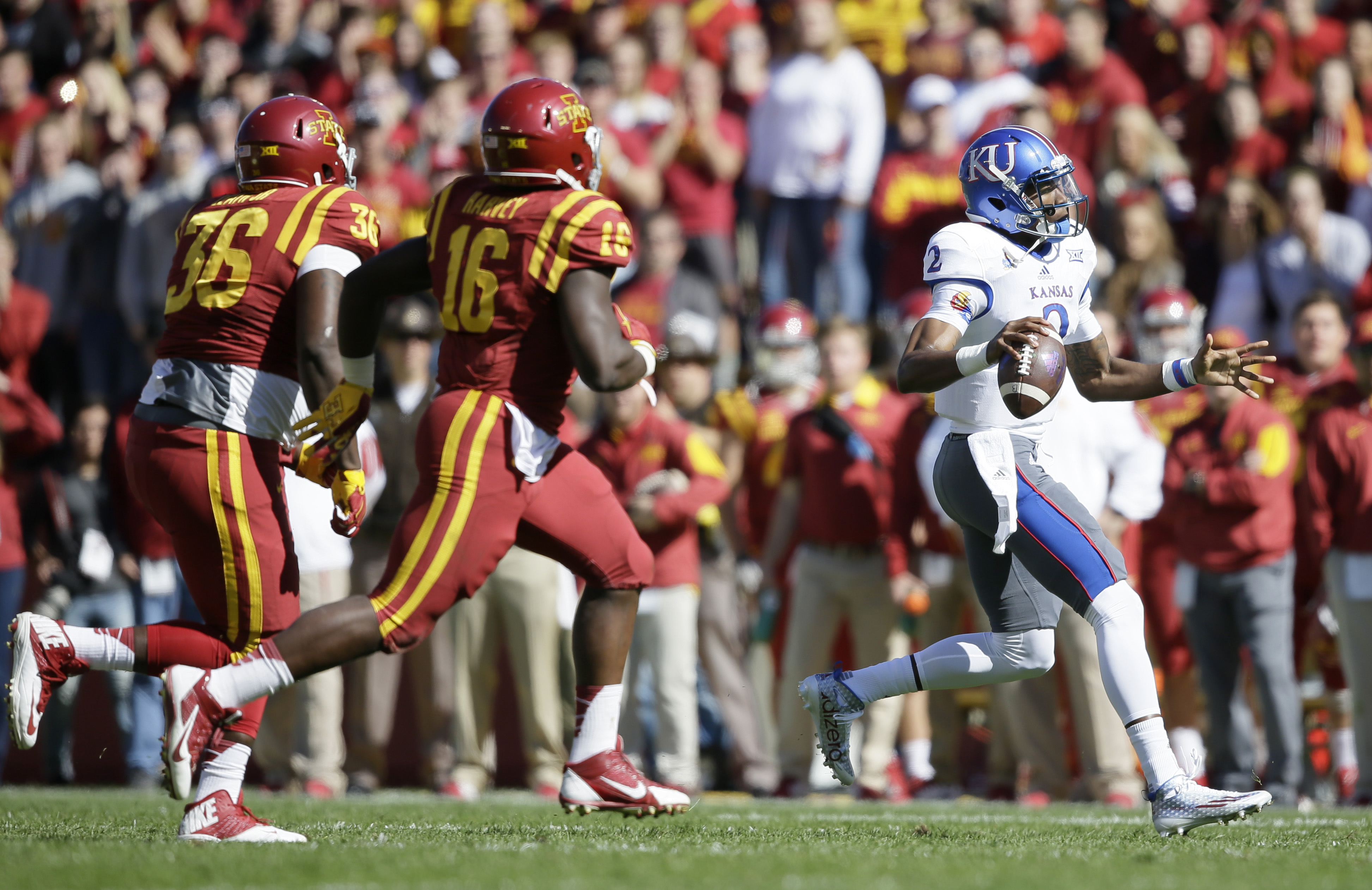 Kansas quarterback Montell Cozart, right, runs from Iowa State defenders Bobby Leath (36) and Willie Harvey (16) during the first half of an NCAA college football game, Saturday, Oct. 3, 2015, in Ames, Iowa. Iowa State won 38-13. (AP Photo/Charlie Neiberg