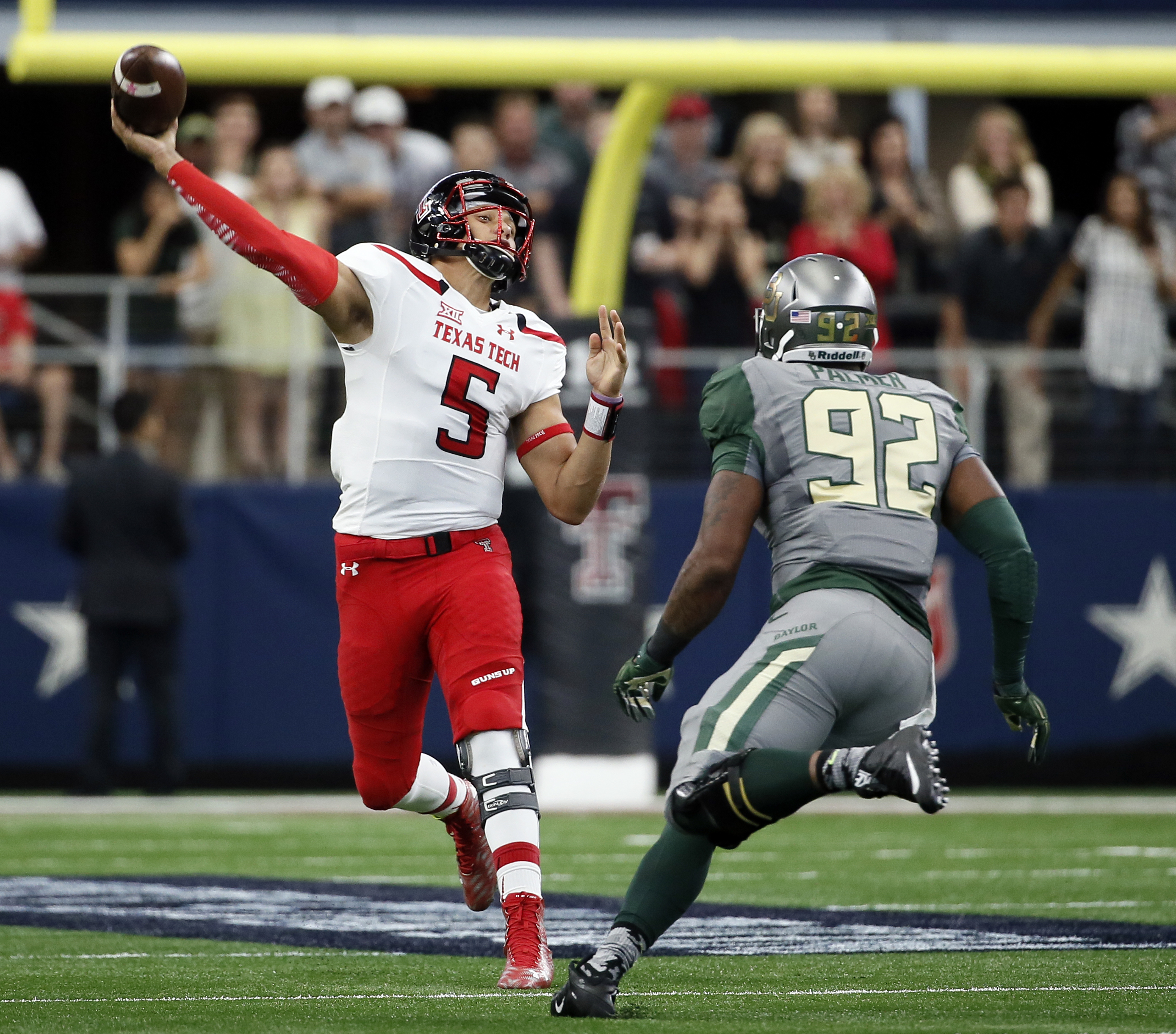 Texas Tech quarterback Patrick Mahomes (5) throws a long touchdown pass to wide receiver Zach Austin under pressure from Baylor defensive end Jamal Palmer (92) in the first half of an NCAA college football game Saturday, Oct. 3, 2015, in Arlington, Texas.