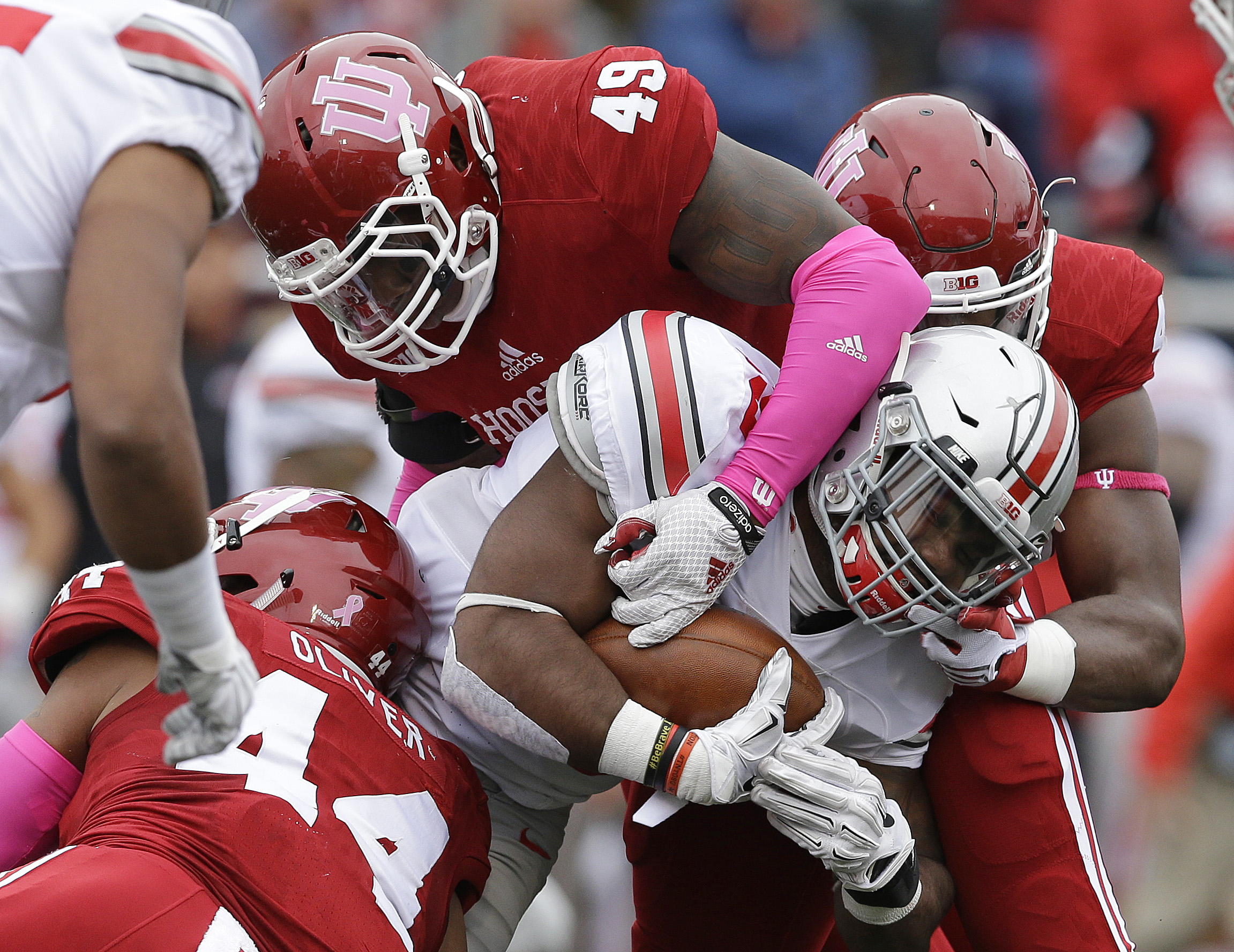 Ohio State's Ezekiel Elliott is tackled by Indiana's Marcus Oliver (44) and Greg Gooch (49) during the first half of an NCAA college football game Saturday, Oct. 3, 2015 in Bloomington, Ind. (AP Photo/Darron Cummings)