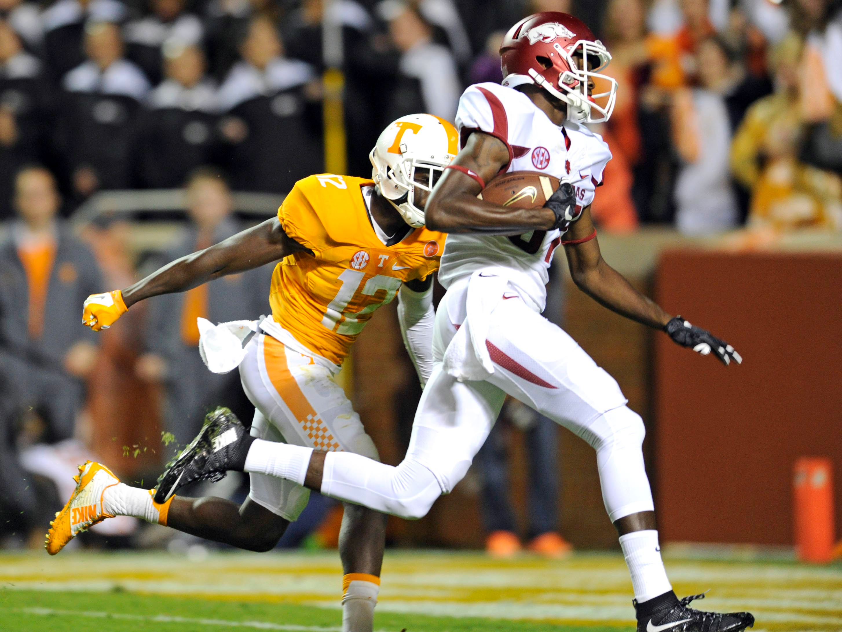 Arkansas wide receiver Dominique Reed (87) scores a touchdown past Tennessee defensive back Emmanuel Moseley (12), tying the score  during the first half of an NCAA college football game at Neyland Stadium in Knoxville, Tenn. on Saturday, Oct. 3, 2015. (A