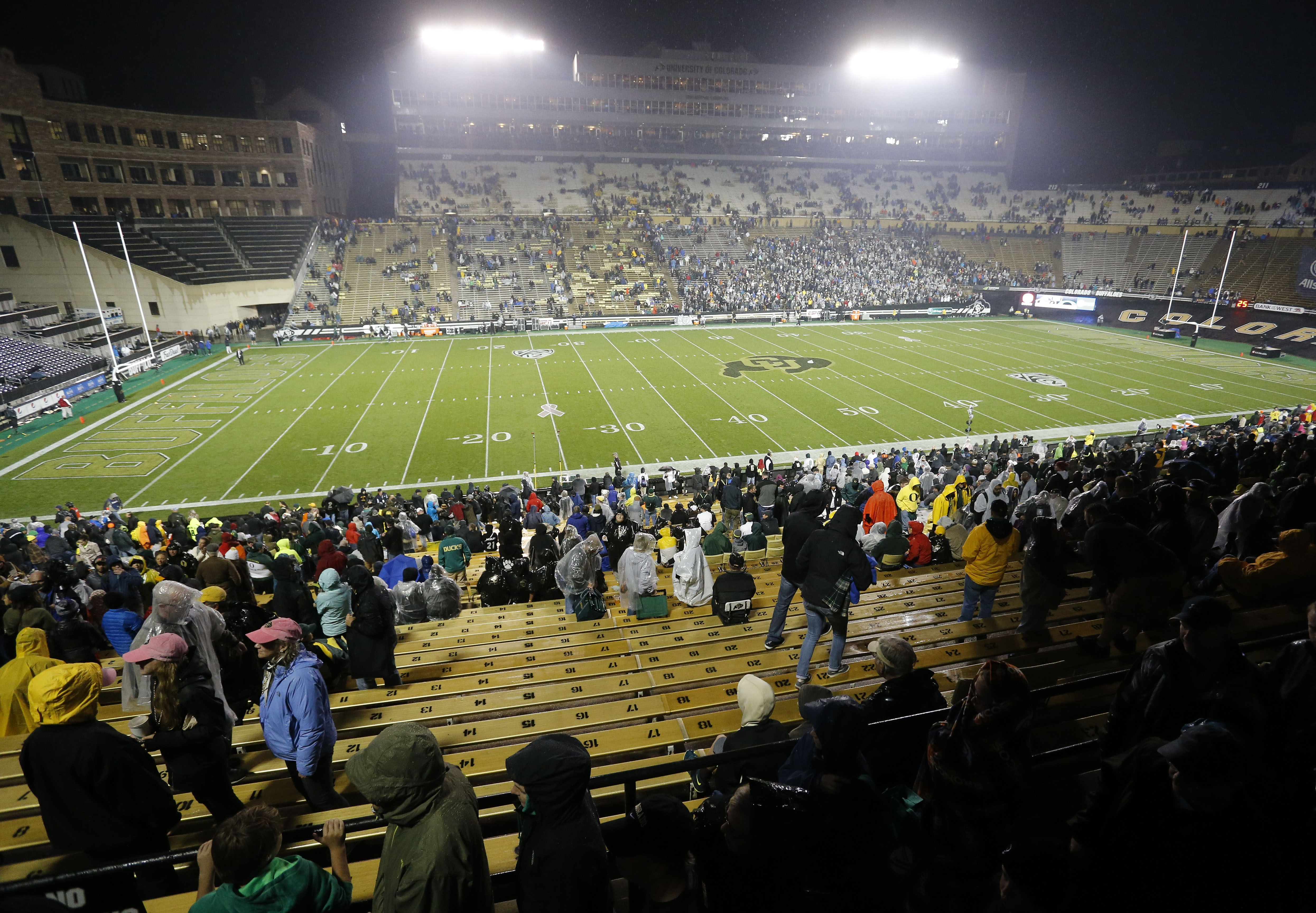 Colorado and Oregon football fans wait out multiple weather delays before an NCAA college football game in Boulder, Colo., Saturday, Oct. 3, 2015. (AP Photo/Brennan Linsley)