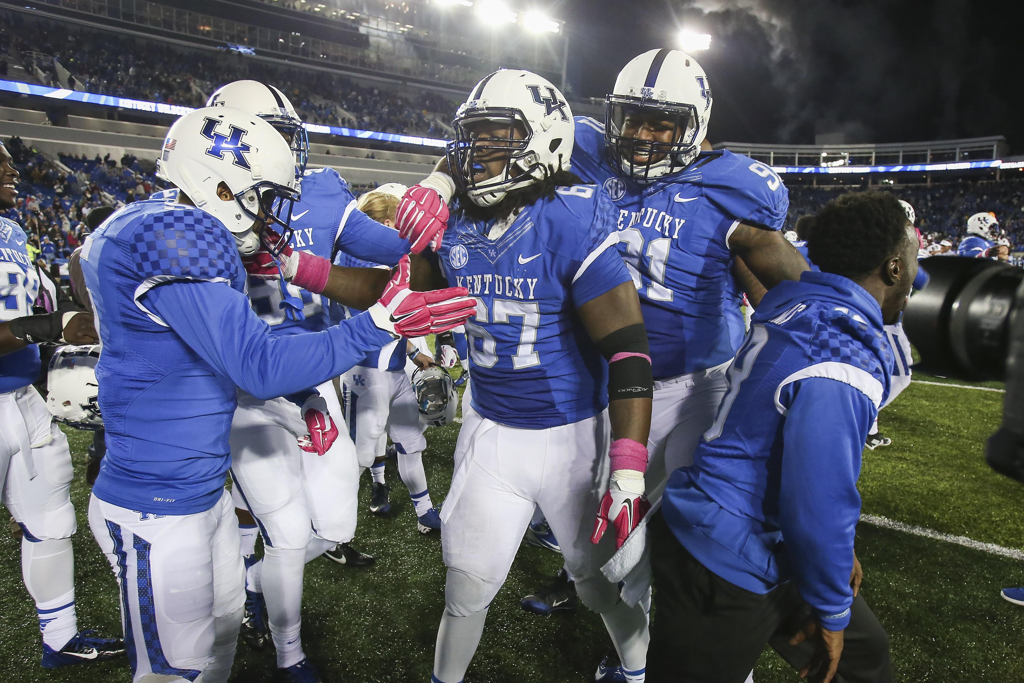 Kentucky cornerback Kendall Randolph, left, defensive tackle Cory Johnson, center, and defensive end Farrington Huguenin celebrate after defeating Eastern Kentucky in overtime during an NCAA college football game Saturday, Oct. 3, 2015, in Lexington, Ky.