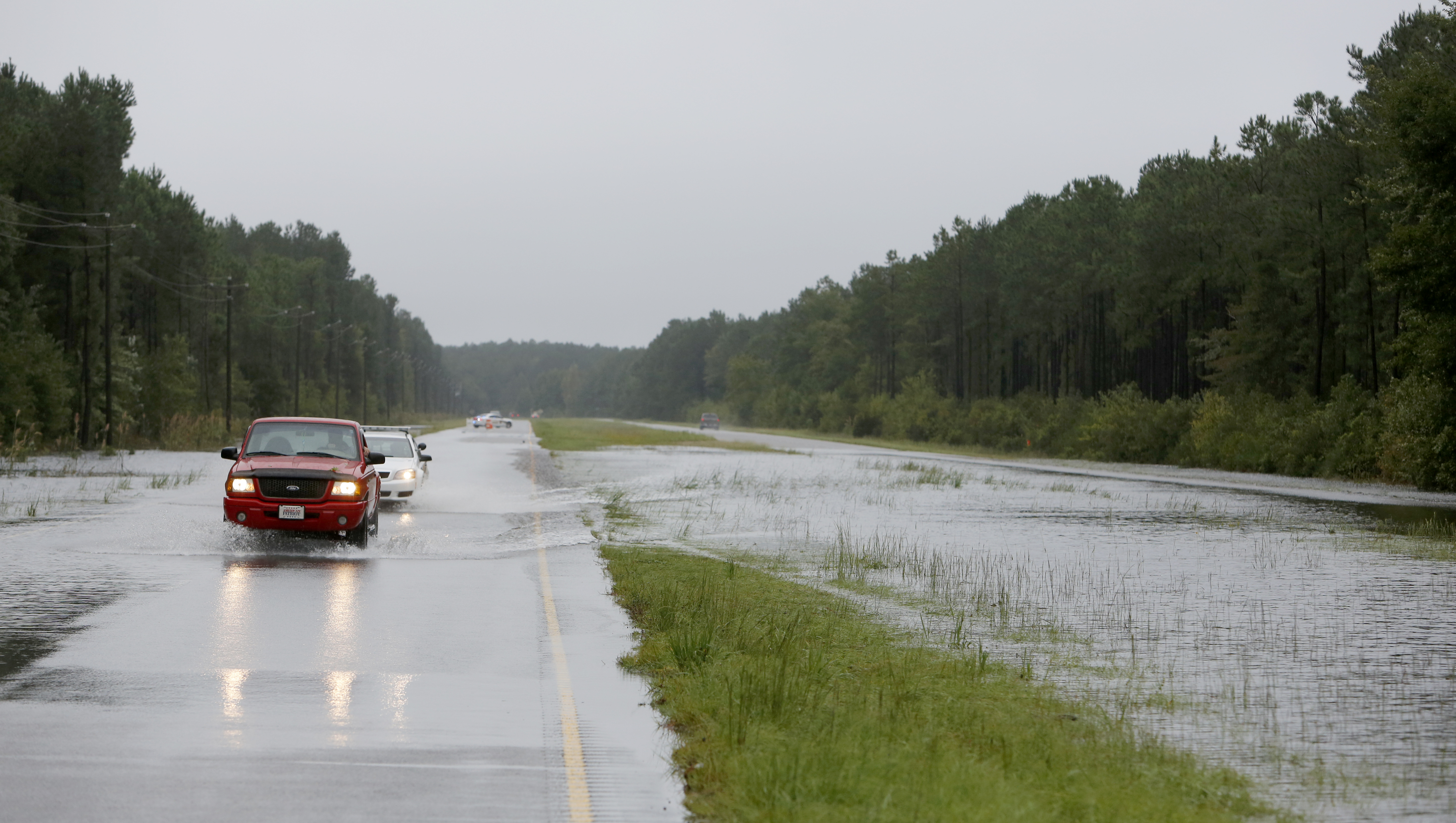 Traffic makes its way through floodwaters on Highway 17 North near Awendaw, S.C., Sunday, Oct. 4, 2015. Several sections of Highway 17 are shut down between Charleston and Georgetown. (AP Photo/Mic Smith)