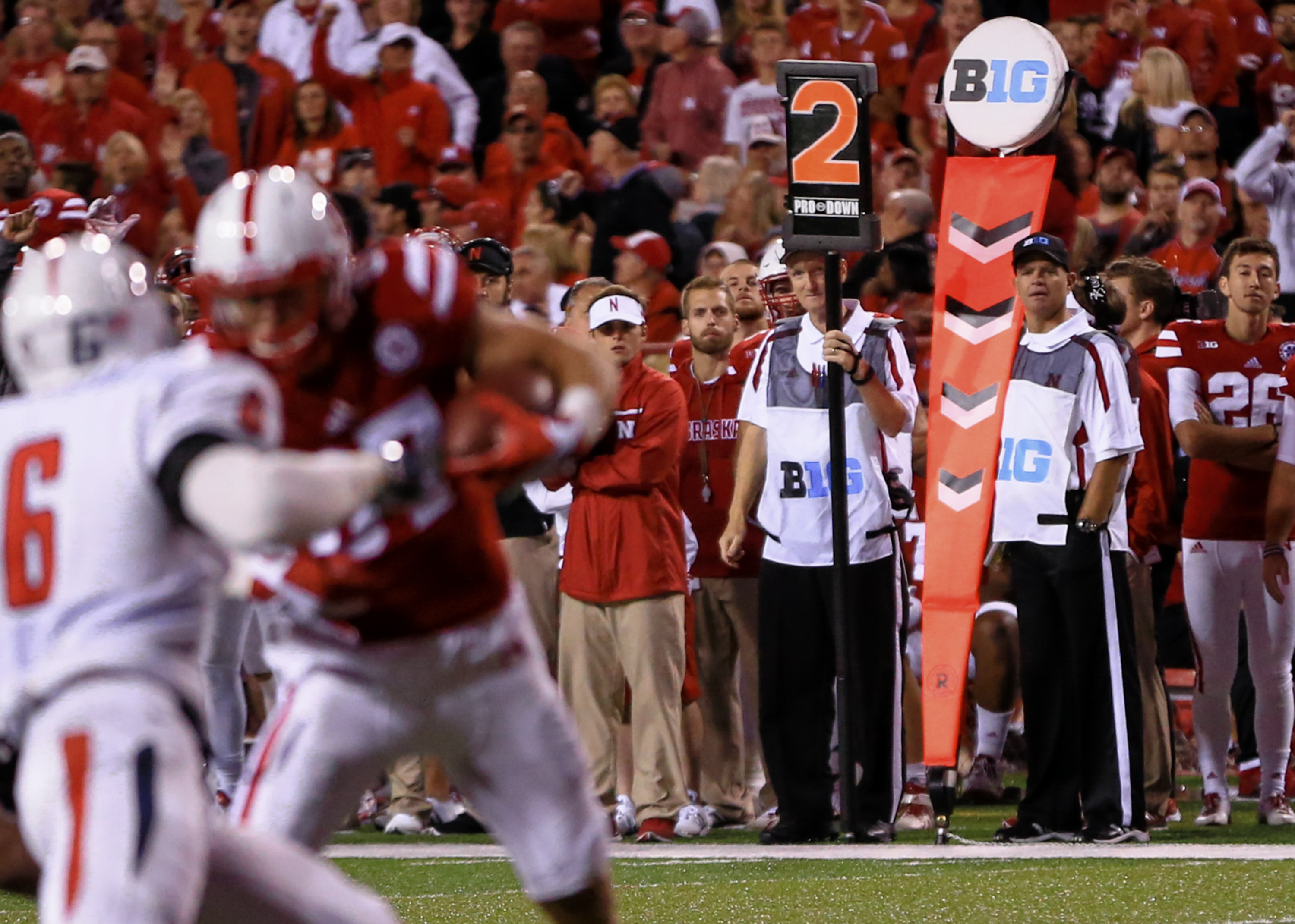 In this Sept. 12, 2015 photo, Big Ten chain gang members Greg Maschman, second right, and Mike Sterns, right, work on the sidelines  in Lincoln, Neb., during an NCAA college football game between Nebraska and South Alabama. The men on the sideline crew, b